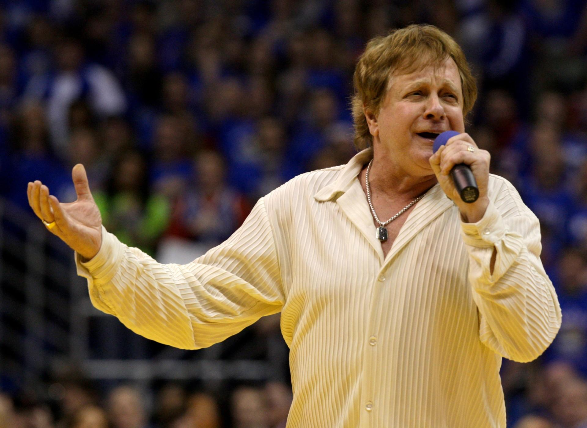 In this Jan. 25, 2010 file photo, Eddie Money sings the national anthem before an NCAA college basketball game between Kansas and Missouri in Lawrence, Kansas. Family members have said Eddie Money has died on Friday, Sept. 13, 2019. (AP Photo / Charlie Riedel, File)
