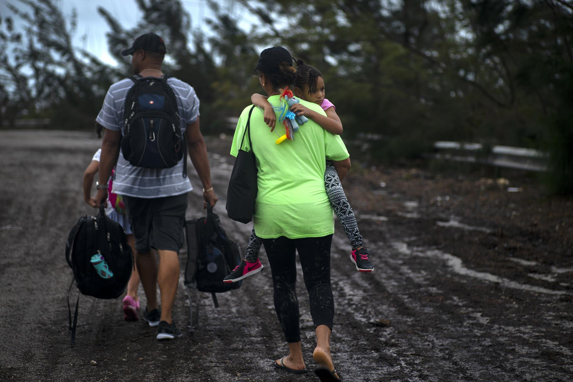 A family walks on a road after being rescued from the floodwaters of Hurricane Dorian, near Freeport, Grand Bahama, Bahamas on Tuesday Sept. 3, 2019. They were rescued by volunteers who drove a bus into the floodwaters to pick them up. (AP Photo / Ramon Espinosa)