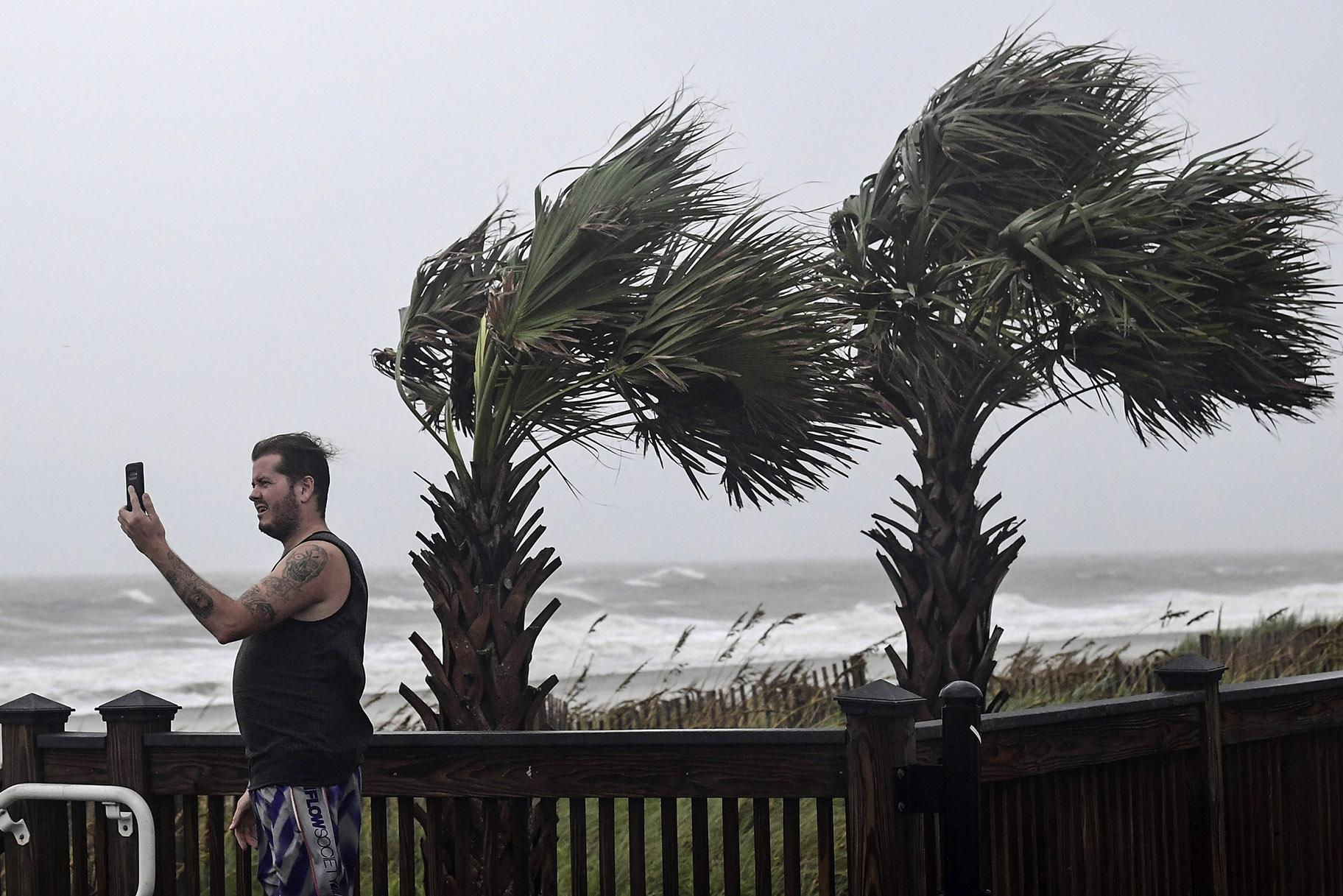 William Ellinge, of Murrells Inlet, S.C., takes photos of waves crashing on the shore in Myrtle Beach, S.C., Thursday, Sept. 5, 2019, as Hurricane Dorian moves north off the coast. (Ken Ruinard / The Independent-Mail via AP)