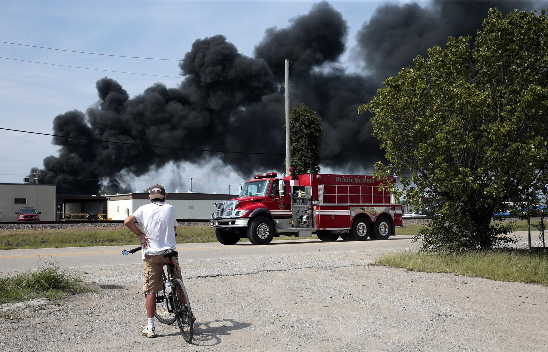 A resident watches as a fire truck arrives in downtown Dupo, Illinois, to help fight a tanker fire from a derailed train on Tuesday, Sept. 10. 2019. Black smoke coming from the derailment scene can be seen for miles and caused the evacuation of schools in the town, authorities said. (Robert Cohen / St. Louis Post-Dispatch via AP)