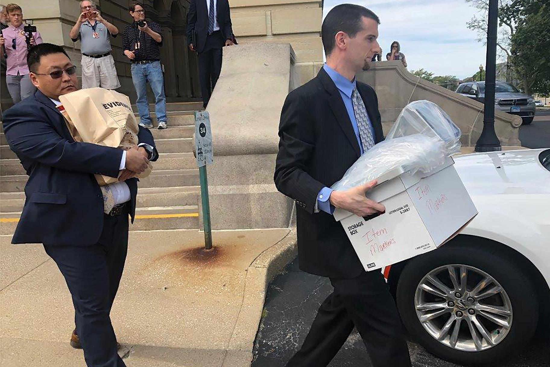 "Men carrying boxes and a bag marked ""evidence"" leave the Illinois State Capitol on Tuesday, Sept. 24, 2019 after a raid at the office of state Sen. Martin Sandoval. (AP Photo/John O'Connor, File)"