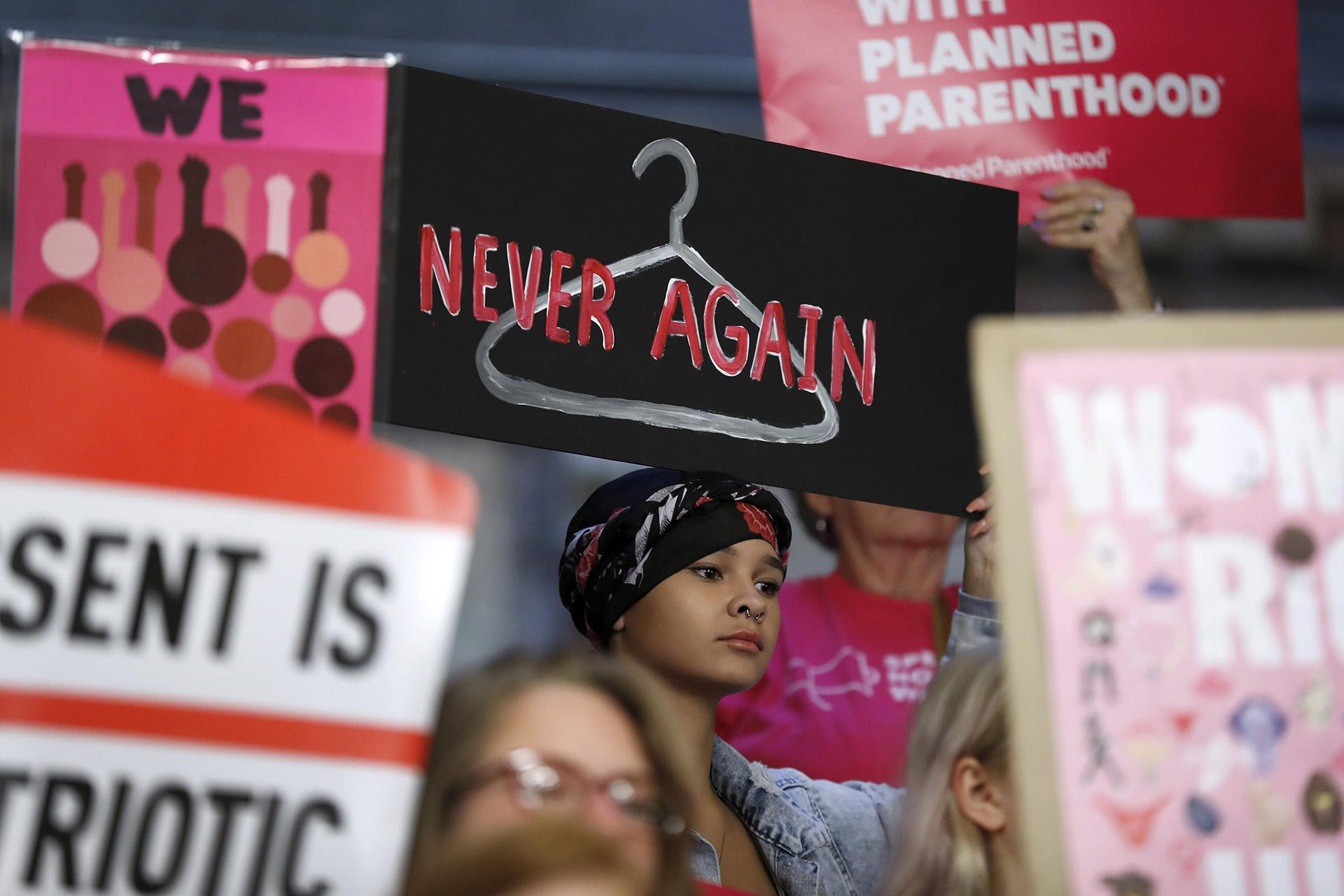 In this Tuesday, May 21, 2019 file photo, August Mulvihill, of Norwalk, Iowa, center, holds a sign depicting a wire clothes hanger during a rally at the Statehouse in Des Moines, Iowa, to protest recent abortion bans. (AP Photo / Charlie Neibergall)
