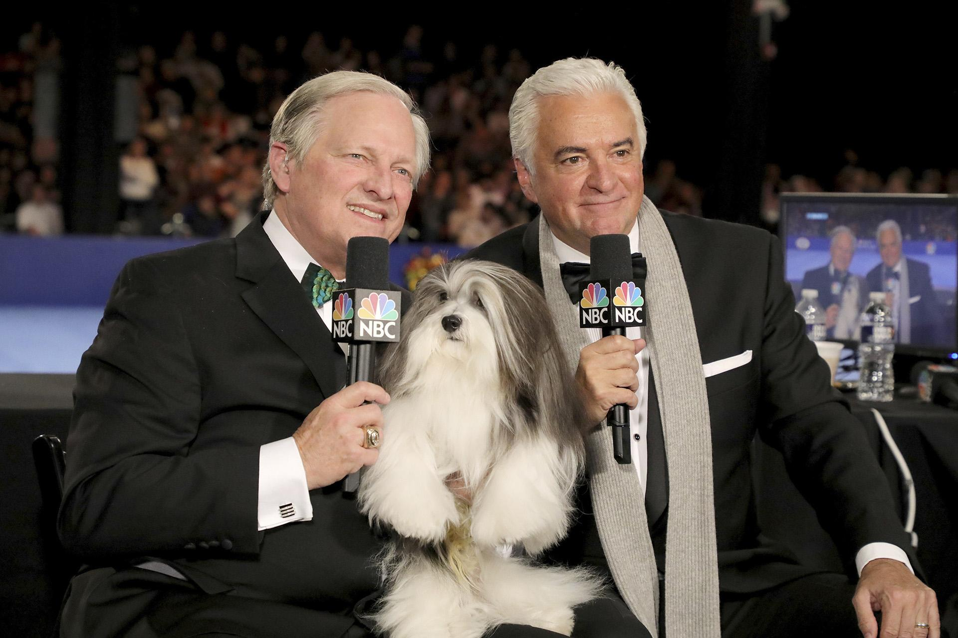 This image released by NBC shows David Frei, left, and host John O'Hurley posing with a havanese dog at The National Dog Show in Philadelphia. The annual parade of pooches has become one of the highest-rated shows of Thanksgiving. (Bill McCay / NBC via AP)