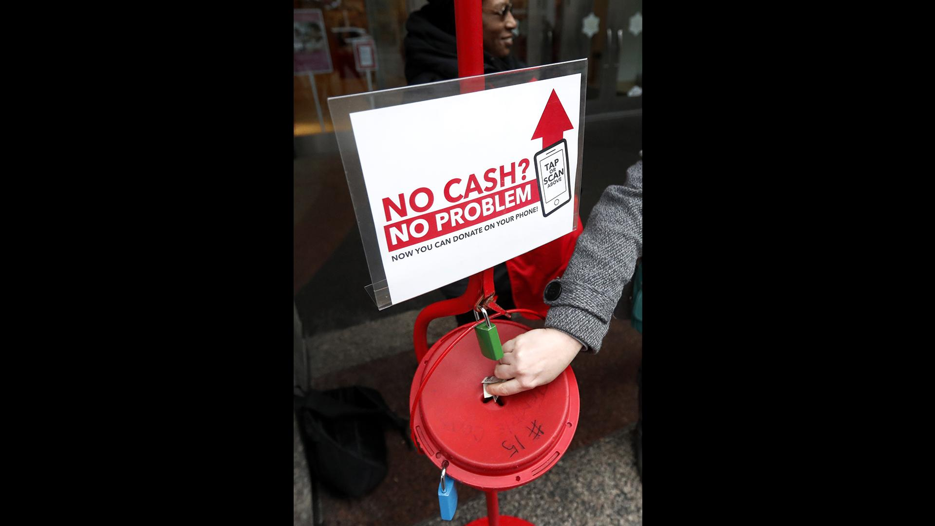 In this Friday, Nov. 15, 2019, photo, a shopper donates cash to the Salvation Army's annual holiday red kettle campaign, with a reminder that mobile contributions are also accepted on Chicago's Magnificent Mile. (AP Photo / Charles Rex Arbogast)