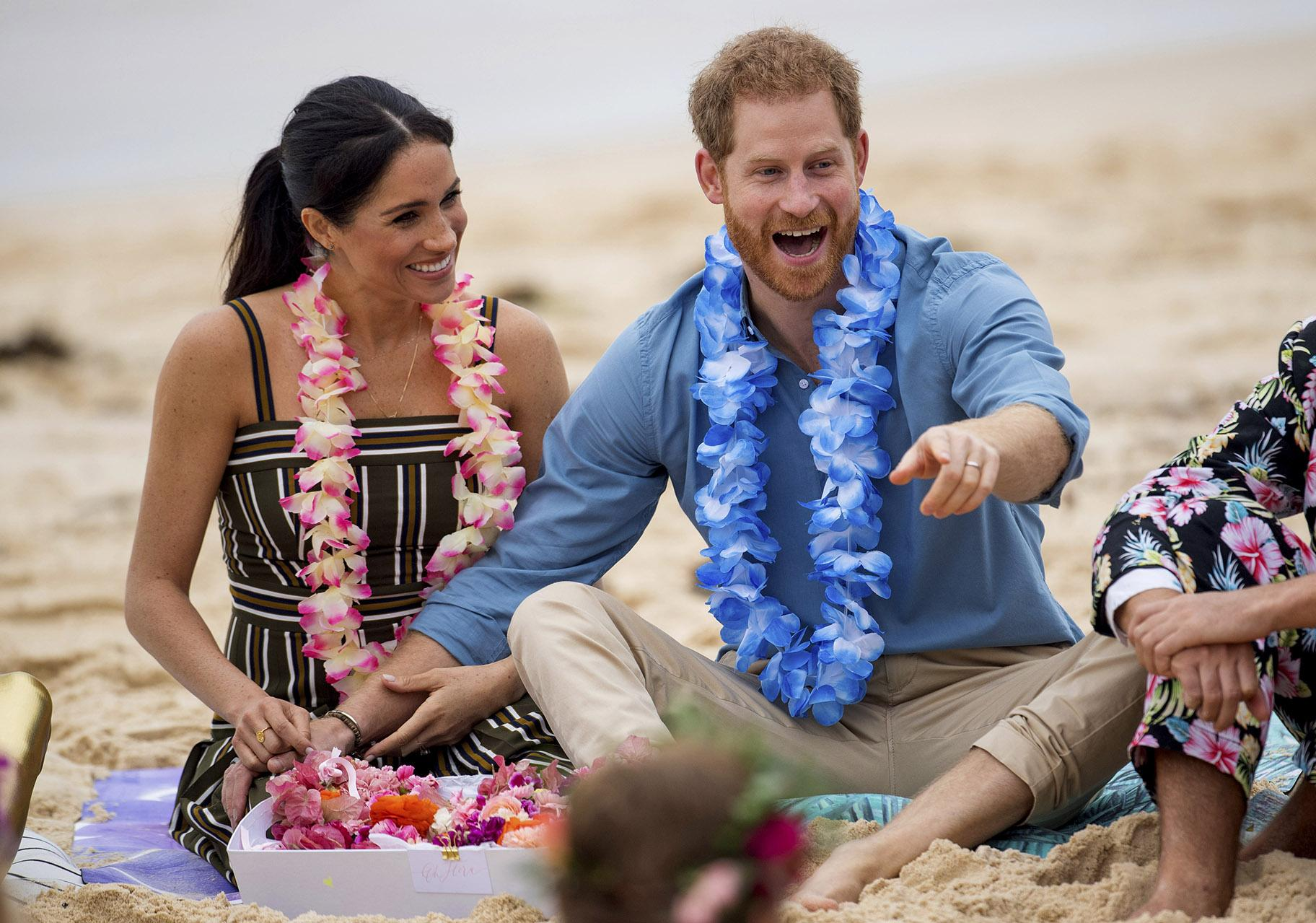 In this Friday, Oct. 19, 2018 file photo, Britain's Prince Harry and Meghan, Duchess of Sussex, meet with a local surfing community group, known as OneWave, raising awareness for mental health and wellbeing in a fun and engaging way at Bondi Beach in Sydney, Australia. (Dominic Lipinski / Pool via AP)