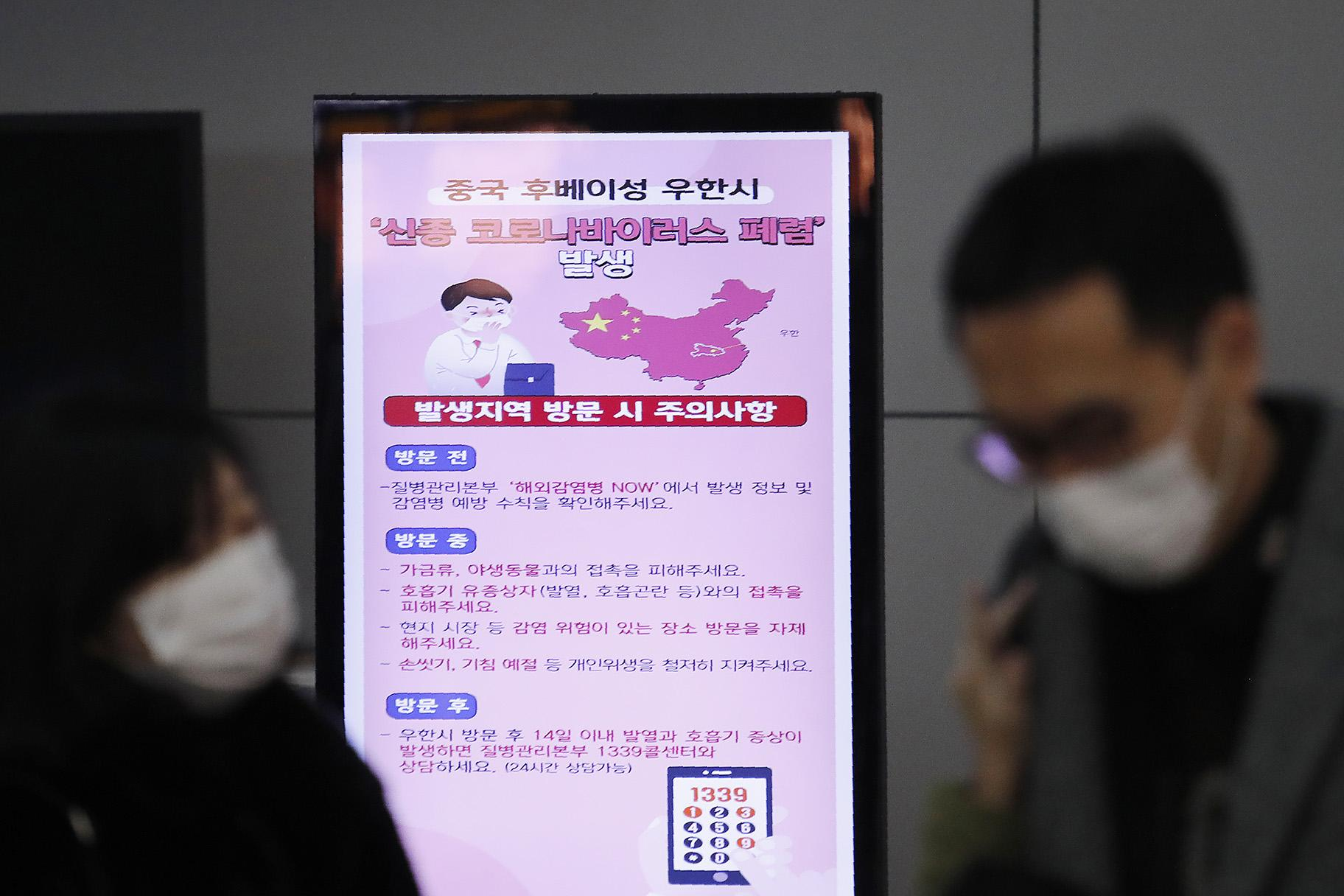 In this Jan. 27, 2020, file photo, a poster warning about coronavirus is seen as passengers wear masks in a departure lobby at Incheon International Airport in Incheon, South Korea. (AP Photo / Ahn Young-joon, File)