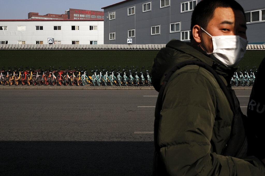 A man wearing a mask stands near a pile of bicycles from bike-sharing companies parked outside a subway station in Beijing, Monday, Feb. 10, 2020. (AP Photo / Andy Wong)