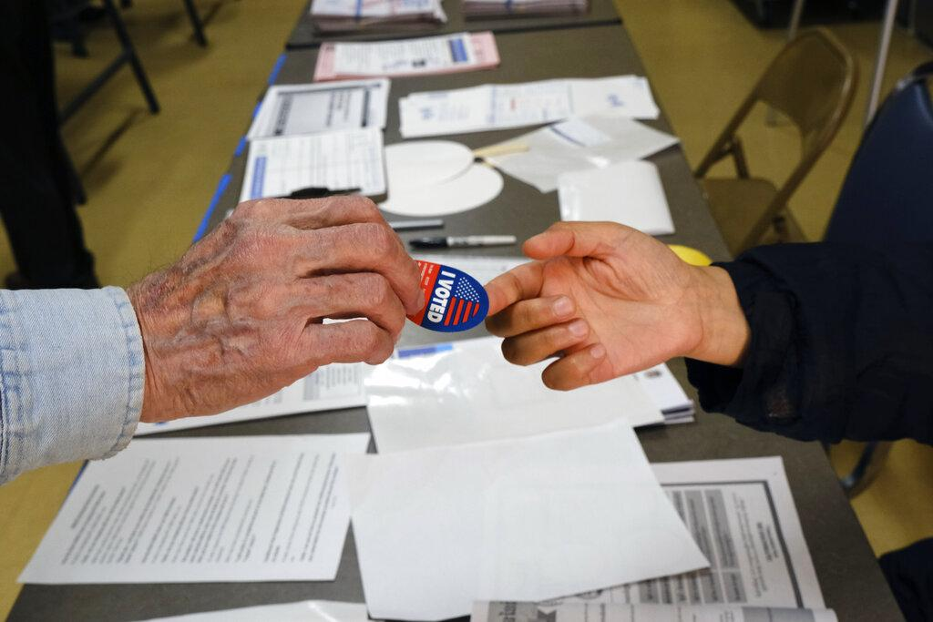 Early voter receives his I-Voted sticker, at an early voting polling station at the Ranchito Avenue Elementary School in the Panorama City section of Los Angeles on Monday, March 2, 2020. (AP Photo / Richard Vogel)