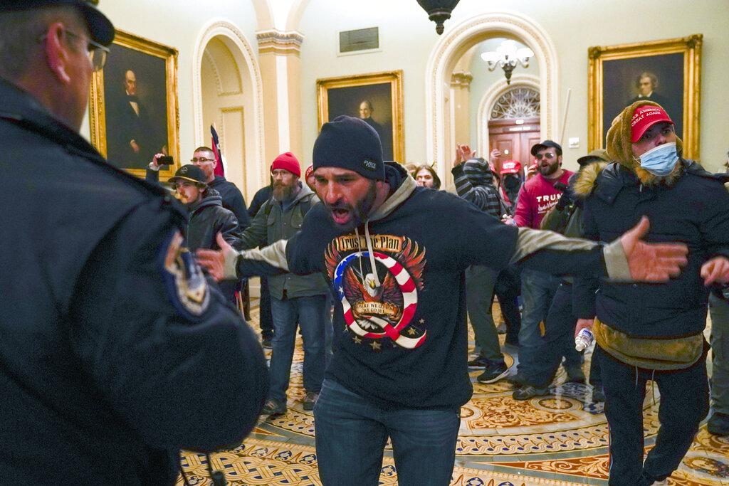 Trump supporters gesture to U.S. Capitol Police in the hallway outside of the Senate chamber at the Capitol in Washington, Wednesday, Jan. 6, 2021. (AP Photo / Manuel Balce Ceneta)