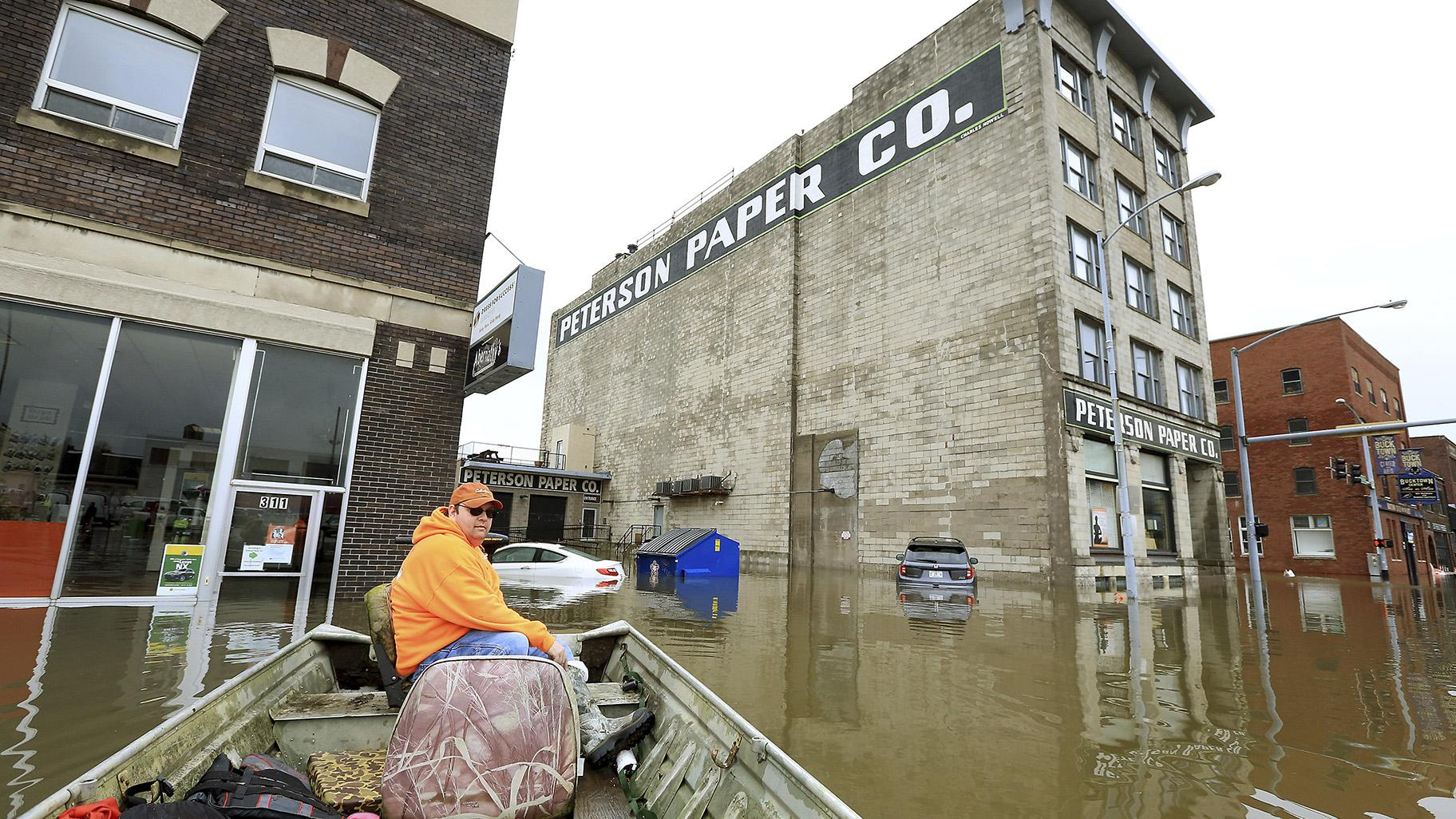 Ryan Lincoln maneuvers his boat through floodwater in downtown Davenport, Iowa, on Thursday, May 2, 2019. (Kevin E. Schmidt / Quad City Times via AP)