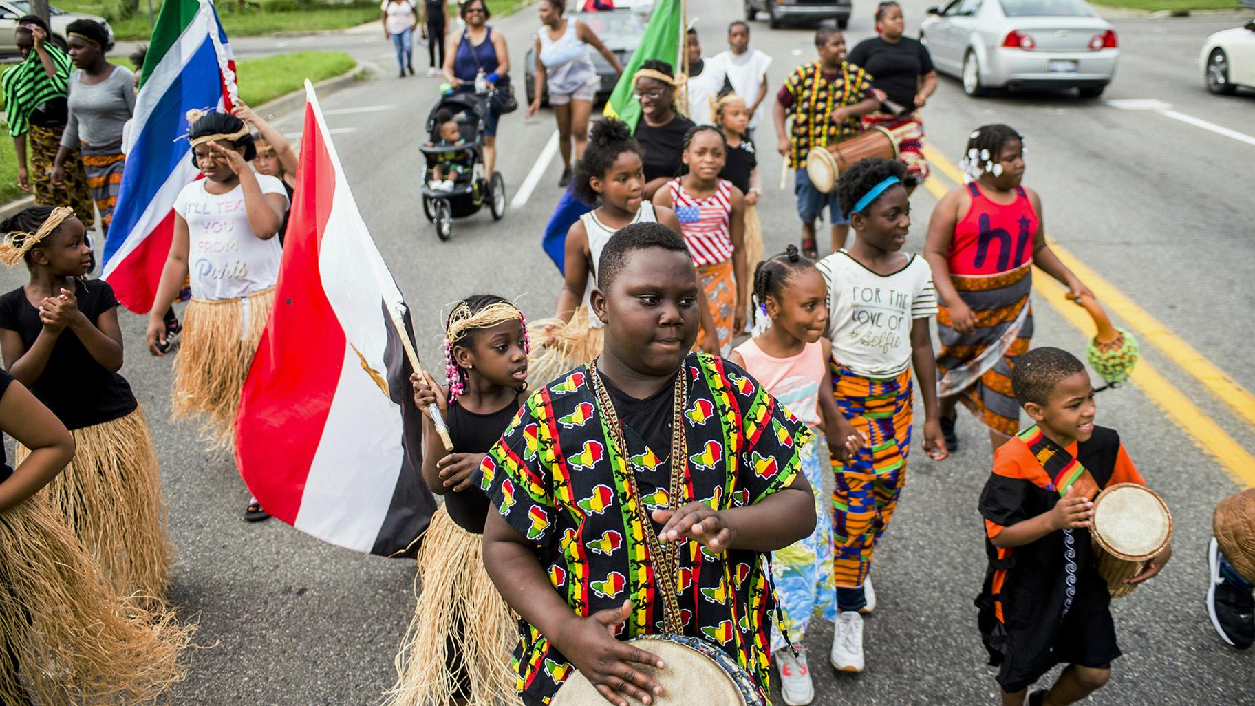 In this June 19, 2018, file photo, Zebiyan Fields, 11, at center, drums alongside more than 20 kids at the front of the Juneteenth parade in Flint, Michigan. (Jake May / The Flint Journal via AP, File)