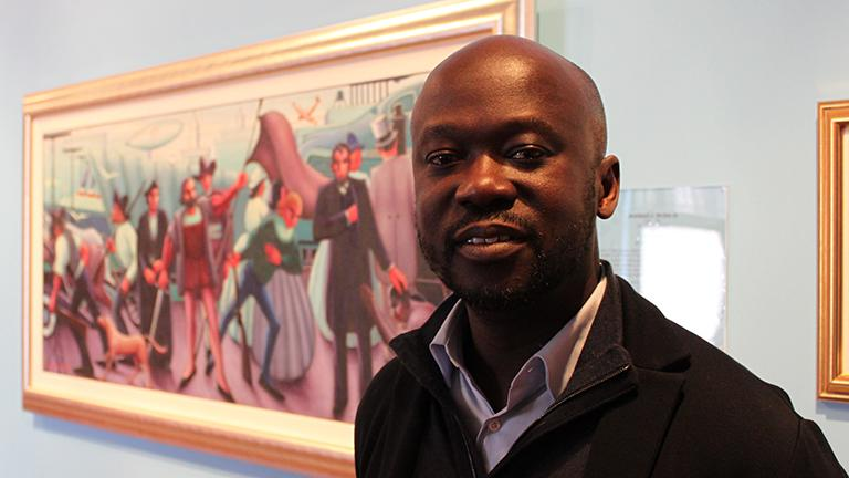 "Architect David Adjaye, a finalist for the Obama Presidential Center, stands before Archibald Motley's ""Progressive America"" at the DuSable Museum on Tuesday."