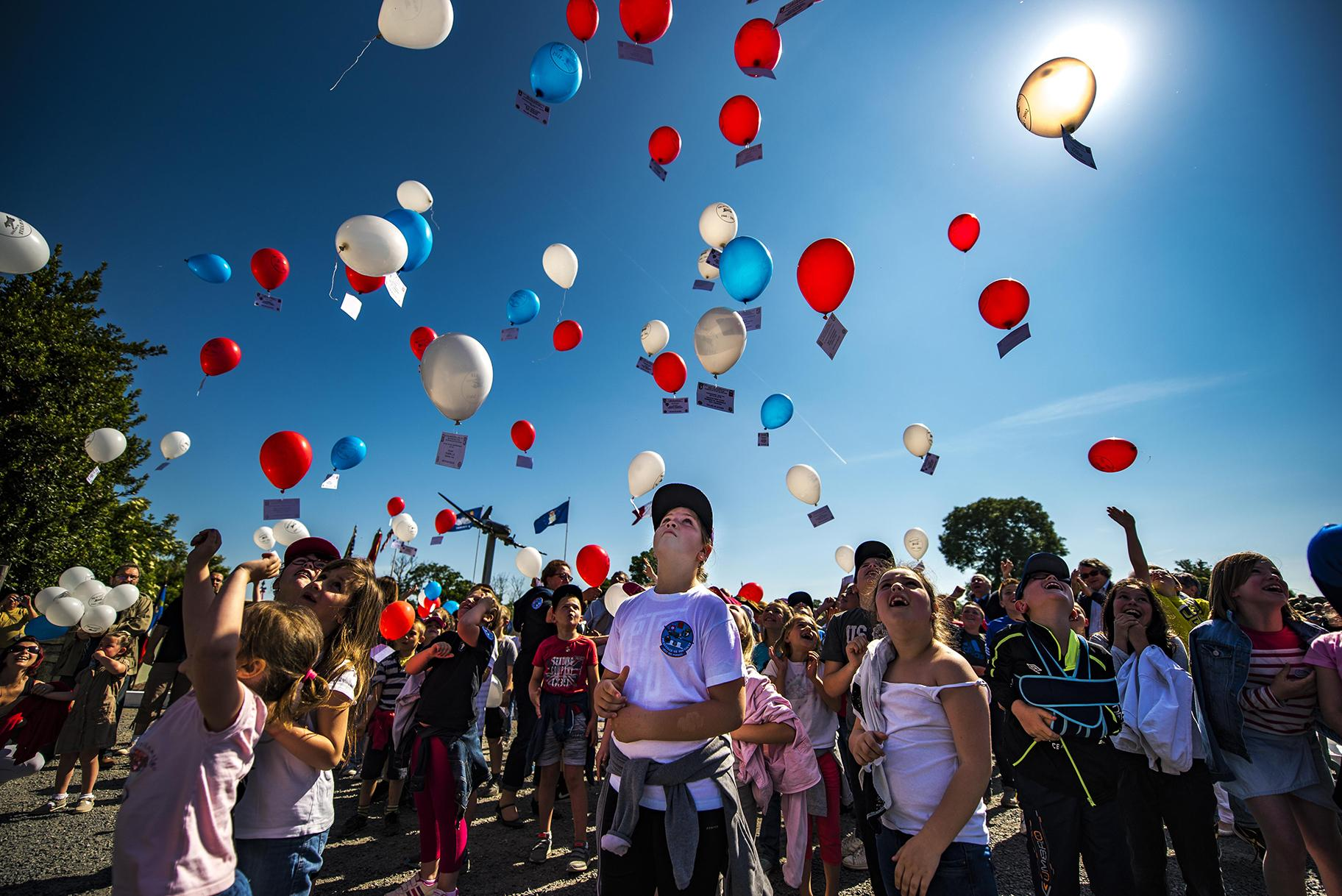 French children release balloons into the air during a D-Day remembrance ceremony at the United States Army Air Forces Transport Memorial in Picauville, France, June 1, 2017. (U.S. Air Force photo / Senior Airman Devin Boyer)