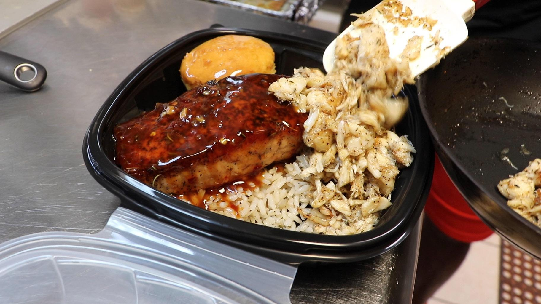 Creole-buttered lump crab meat and pan-seared salmon with sweet chili sauce is placed in a to-go box at Cleo's Southern Cuisine in Chicago's Bronzeville neighborhood on June 27, 2020. (Evan Garcia / WTTW News)