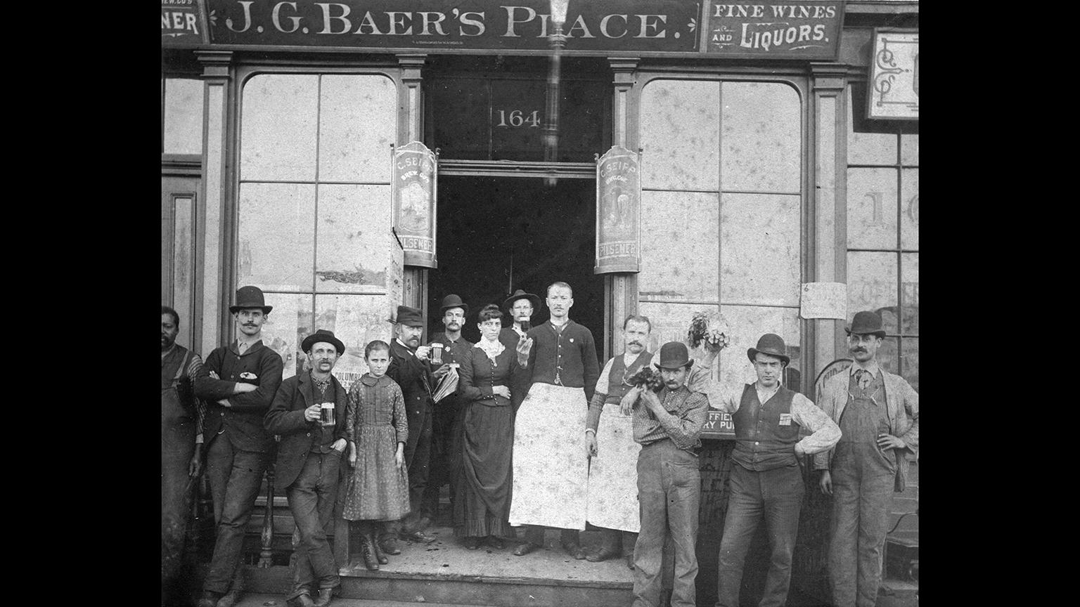 A group of Chicagoans outside J.G. Baer's Place, where signs advertise pilsners made by the C. Seipp Brew Co., which survived the Great Chicago Fire of 1871. (Chicago History Museum)