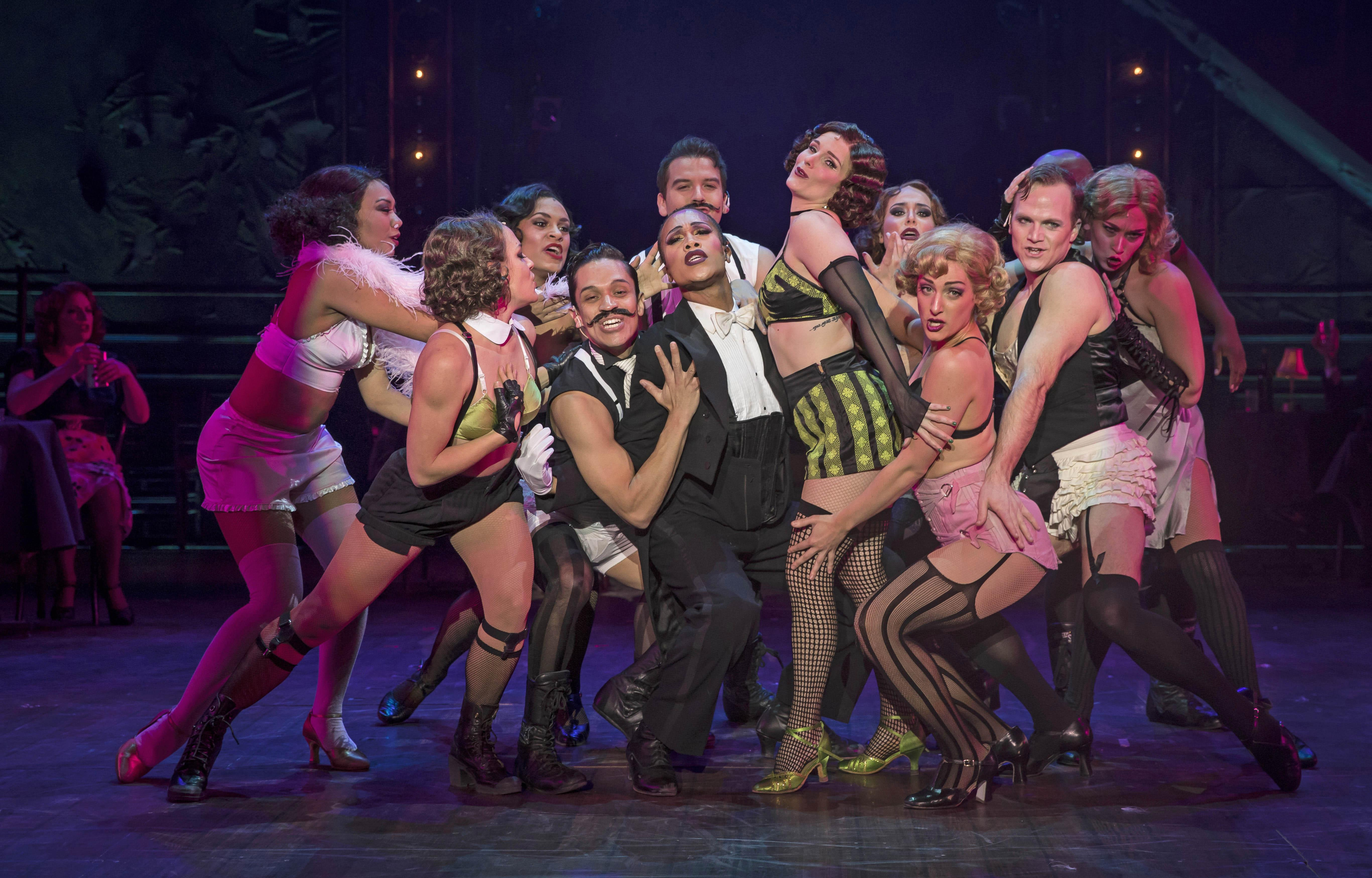 "Joseph Anthony Byrd (center, tux) plays the Emcee and Kelly Felthous (black and green striped shorts) plays Sally Bowles in Paramount Theatre's ""Cabaret."" (Credit: Liz Lauren)"