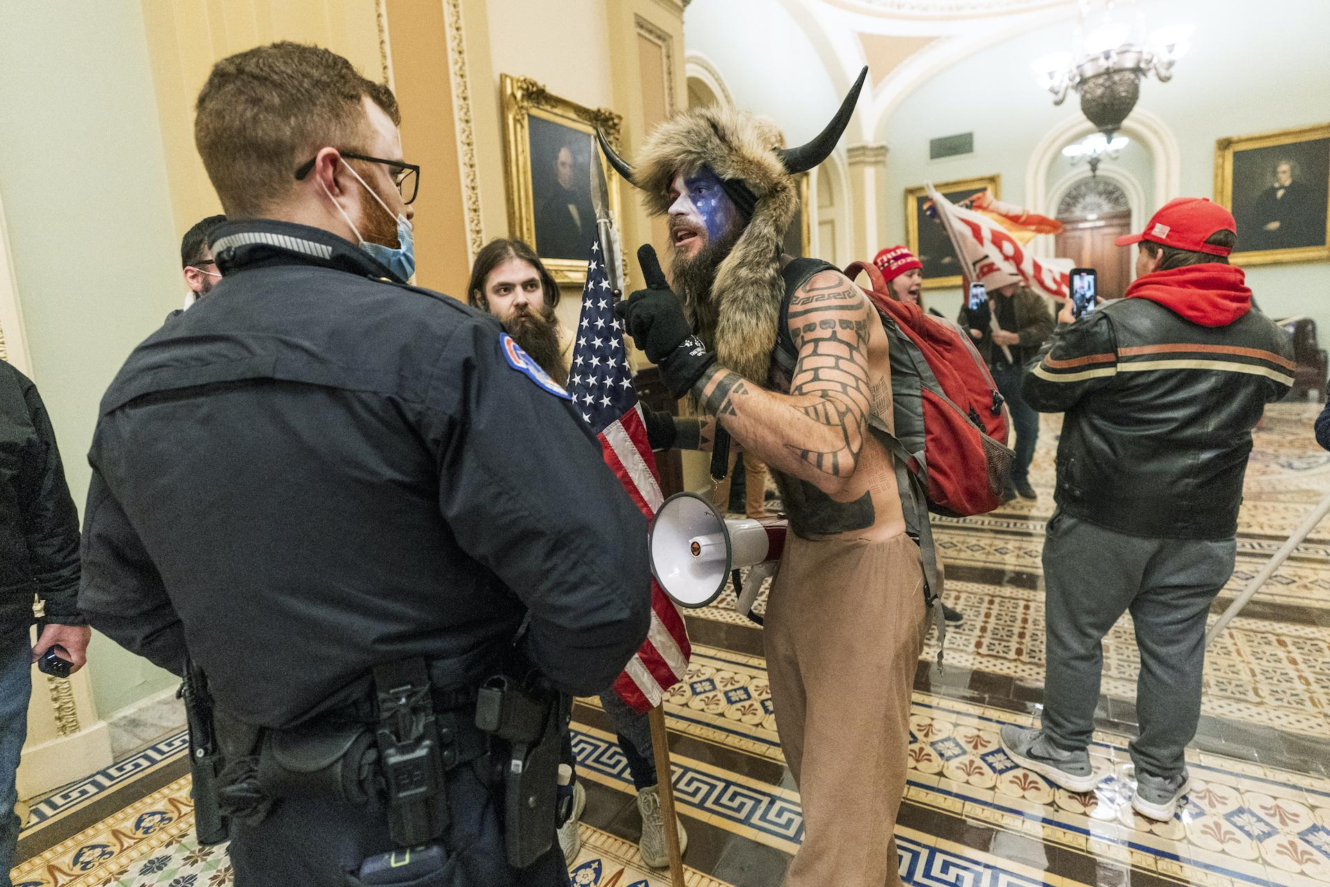 In this Jan. 6, 2021, file photo supporters of President Donald Trump are confronted by U.S. Capitol Police officers outside the Senate Chamber inside the Capitol in Washington. An Arizona man seen in photos and video of the mob wearing a fur hat with horns was also charged Saturday in Wednesday's chaos. Jacob Anthony Chansley, who also goes by the name Jake Angeli, was taken into custody Saturday, Jan. 9. (AP Photo/Manuel Balce Ceneta, File)