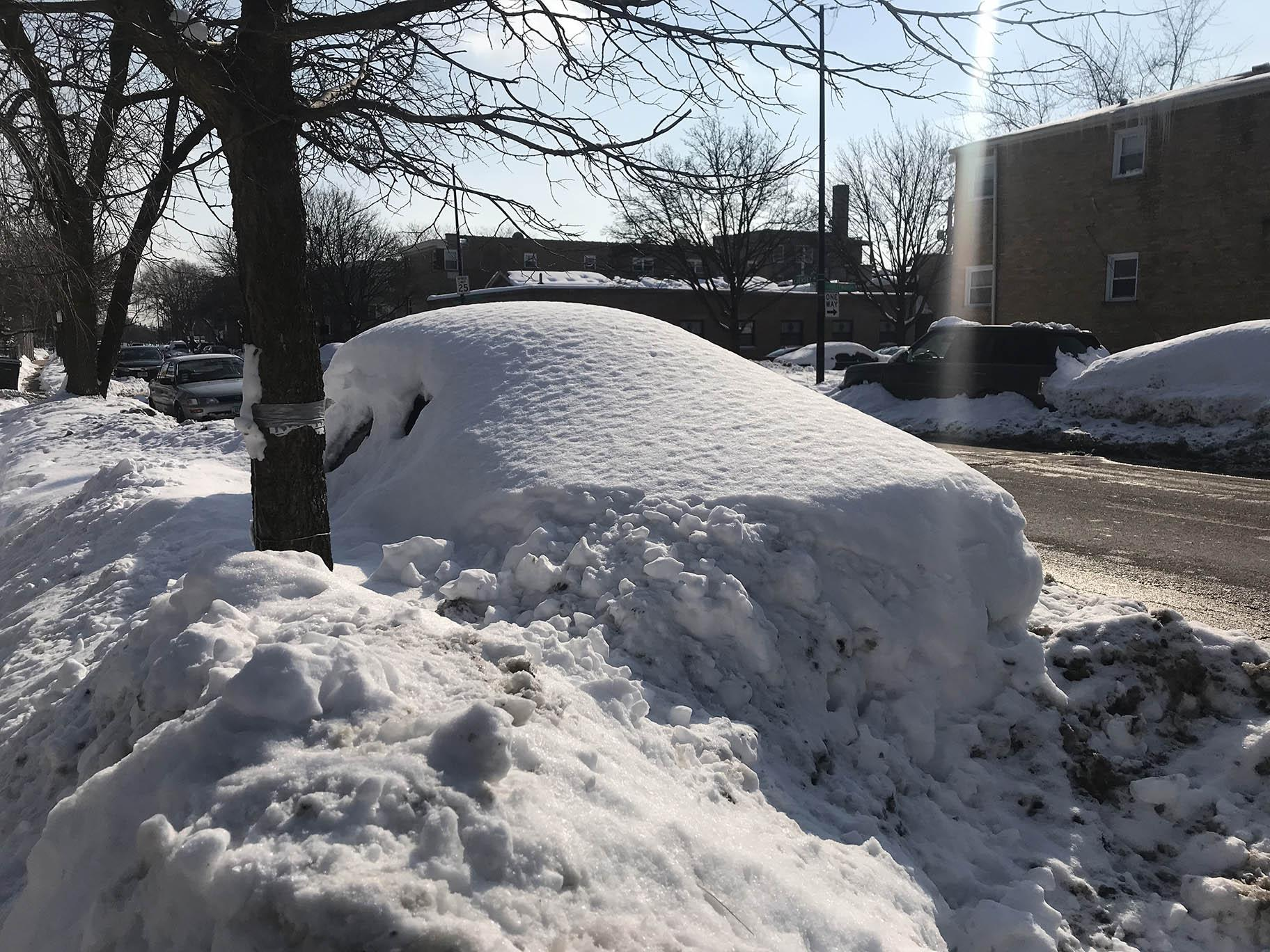 A car parked on a street in Chicago is buried by snow from recent storms. Sunshine and warmer temperatures on Saturday, Feb. 20, 2021 melted some snow, but there is still plenty to shovel. (WTTW News)