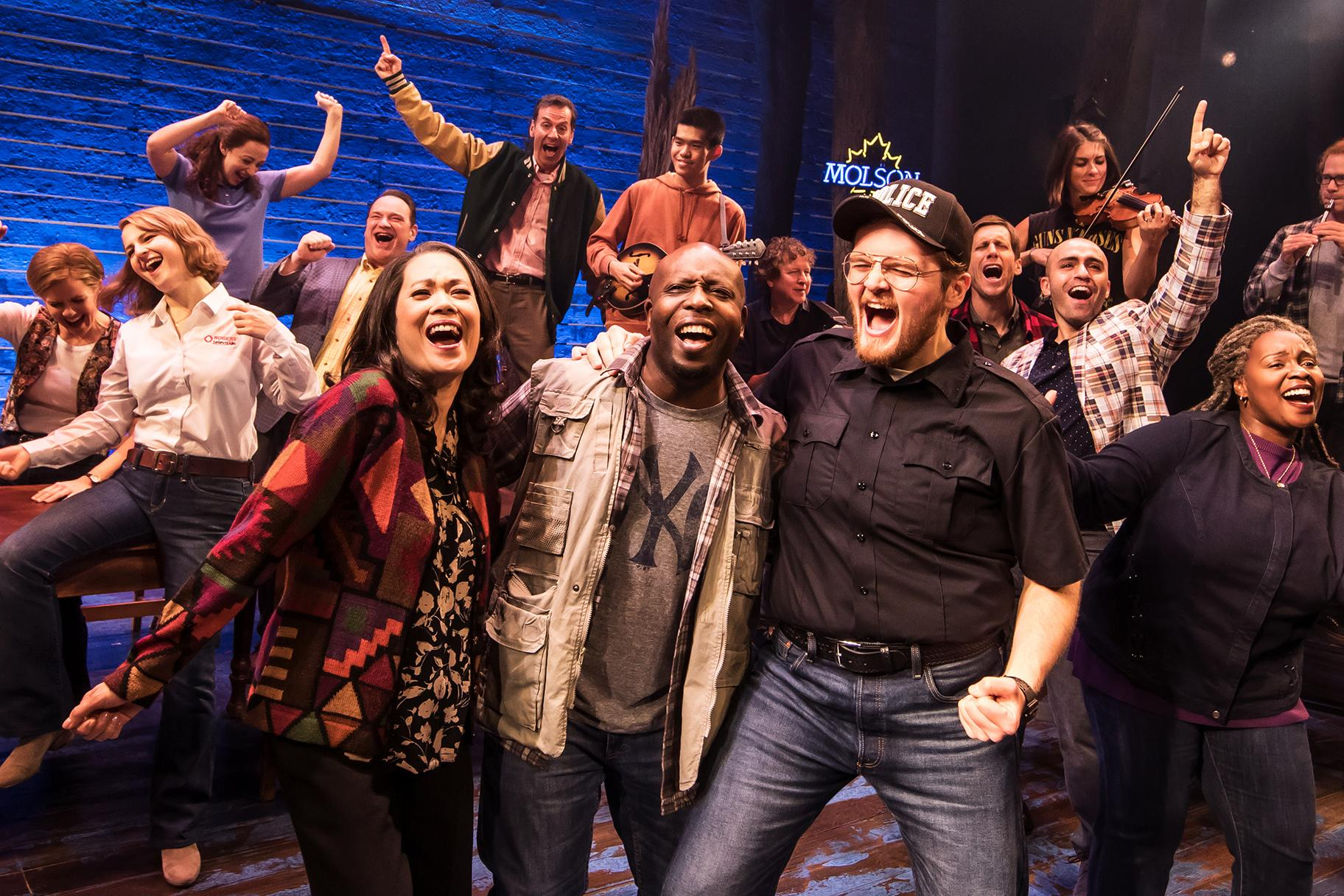 "The 12-person cast in ""Come From Away"" easily morphs in and out of a great array of characters, from stranded travelers from many different countries (not all English-speaking) to the eccentric residents of Gander, Newfoundland, where 38 planes headed to the U.S. were ordered to land. (Photo Credit: Matthew Murphy)"