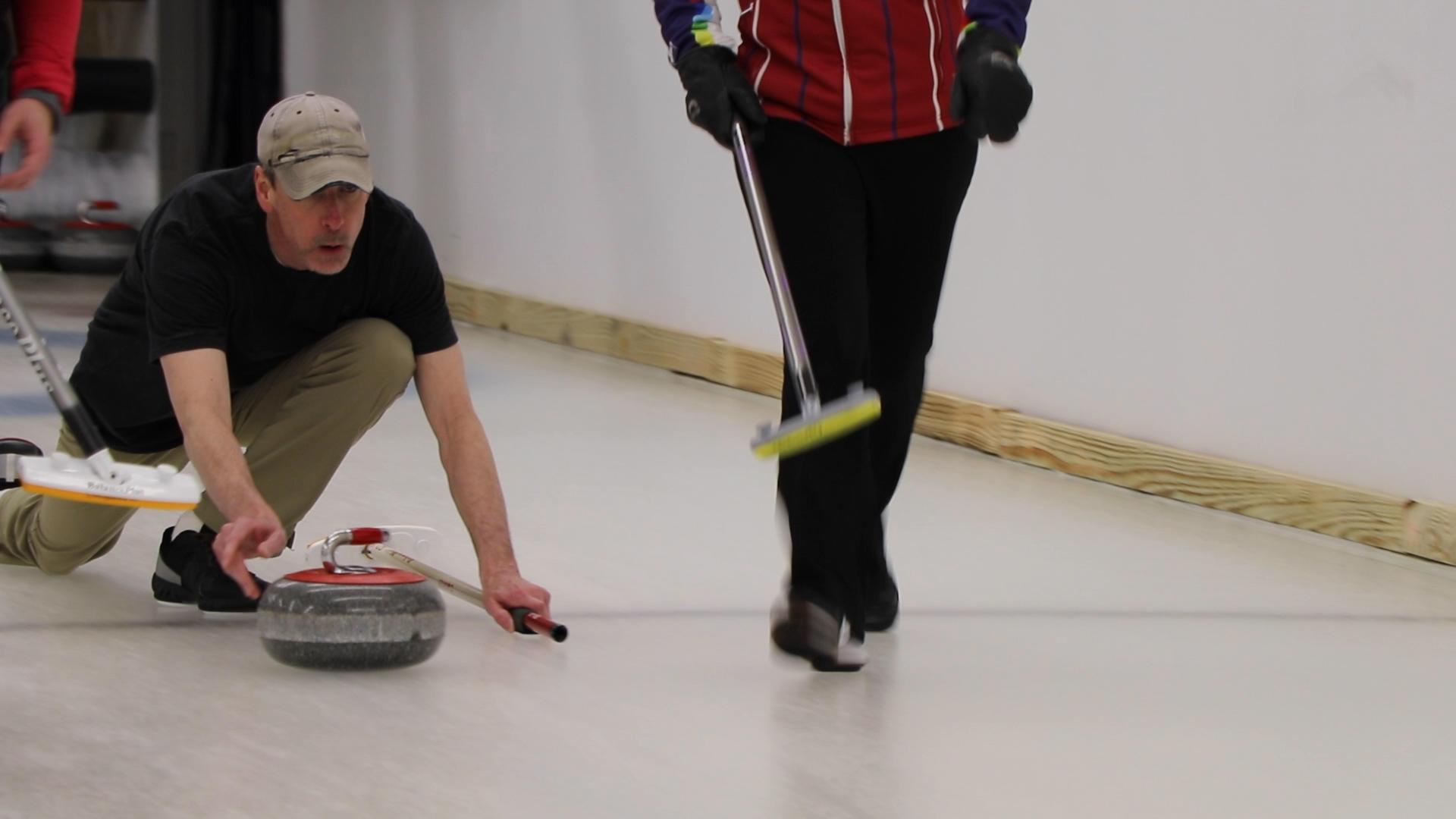 A shooter sends the 42-pound granite curling stone down the sheet of ice. (Evan Garcia / WTTW News)