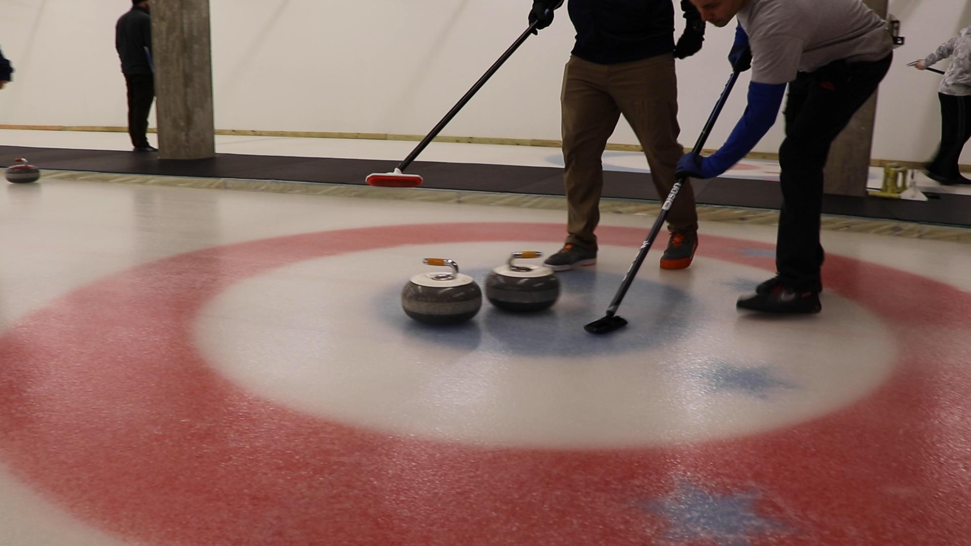 Curlers score when they slide their stone closer to the house's center compared to their opponent. (Evan Garcia / WTTW News)