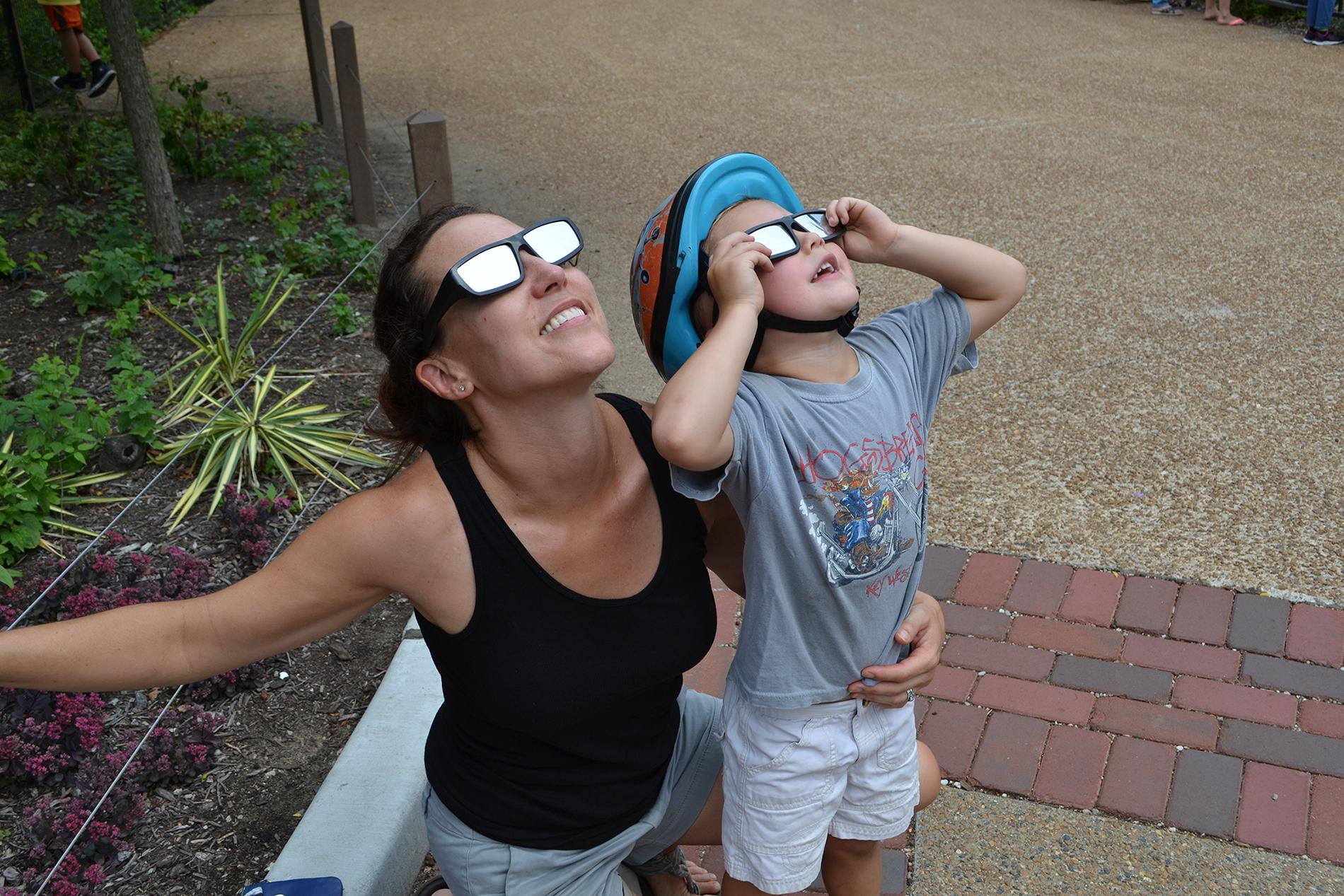 Maria Opdycke and her son, Simm, of Evanston, view the solar eclipse Monday at Lincoln Park Zoo. (Photos by Alex Ruppenthal / Chicago Tonight)