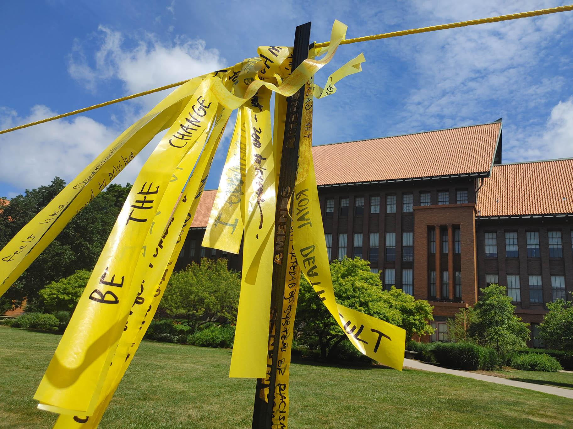 "Handwritten messages on yellow ribbon comprise ""Dirty Laundry"" on the lawn at Schurz High School. (Erica Gunderson / WTTW News)"
