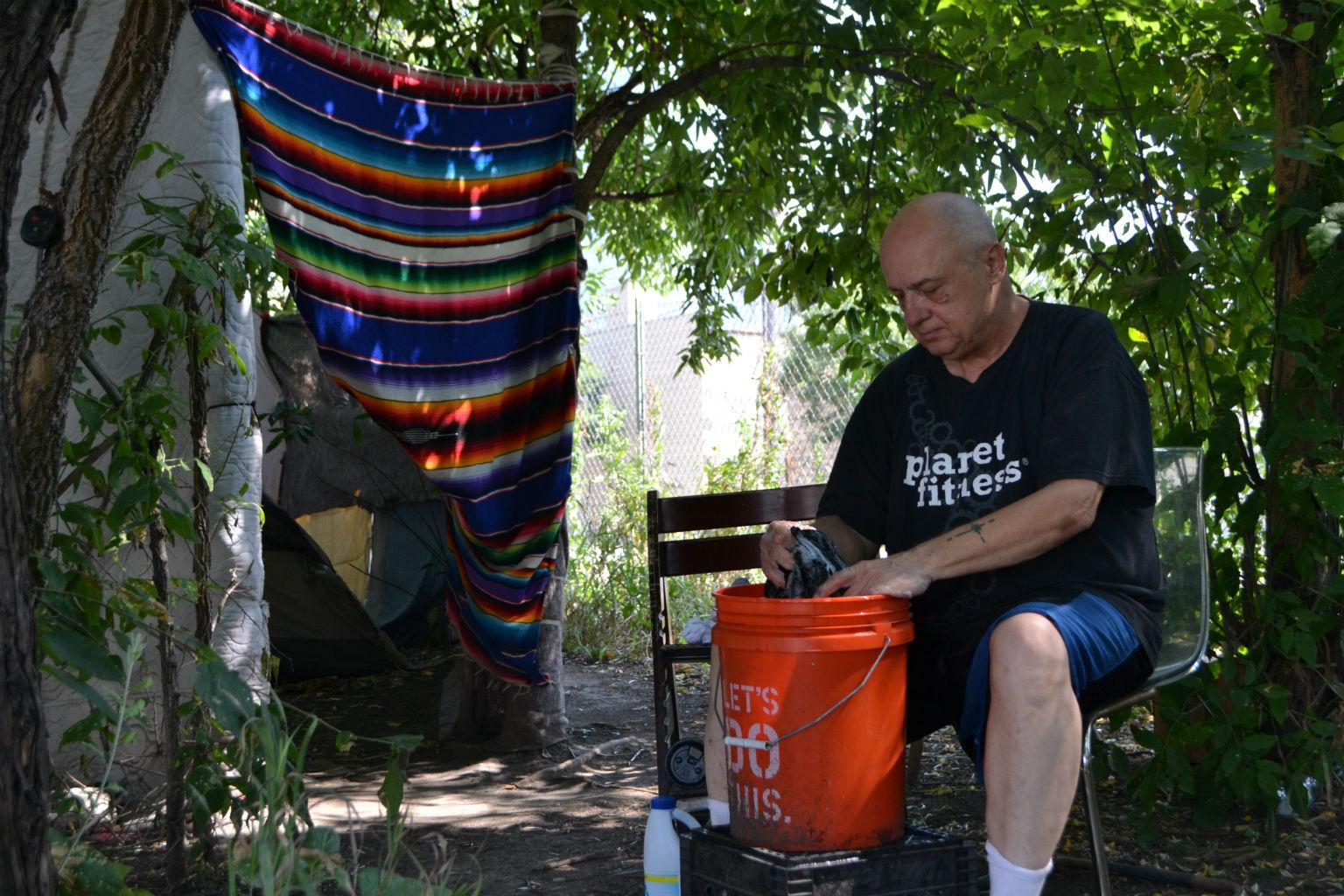 Don Gorobegko washes clothes Friday, Aug. 10, 2018, in a homeless encampment along DesPlaines Street. (Kristen Thometz / Chicago Tonight)