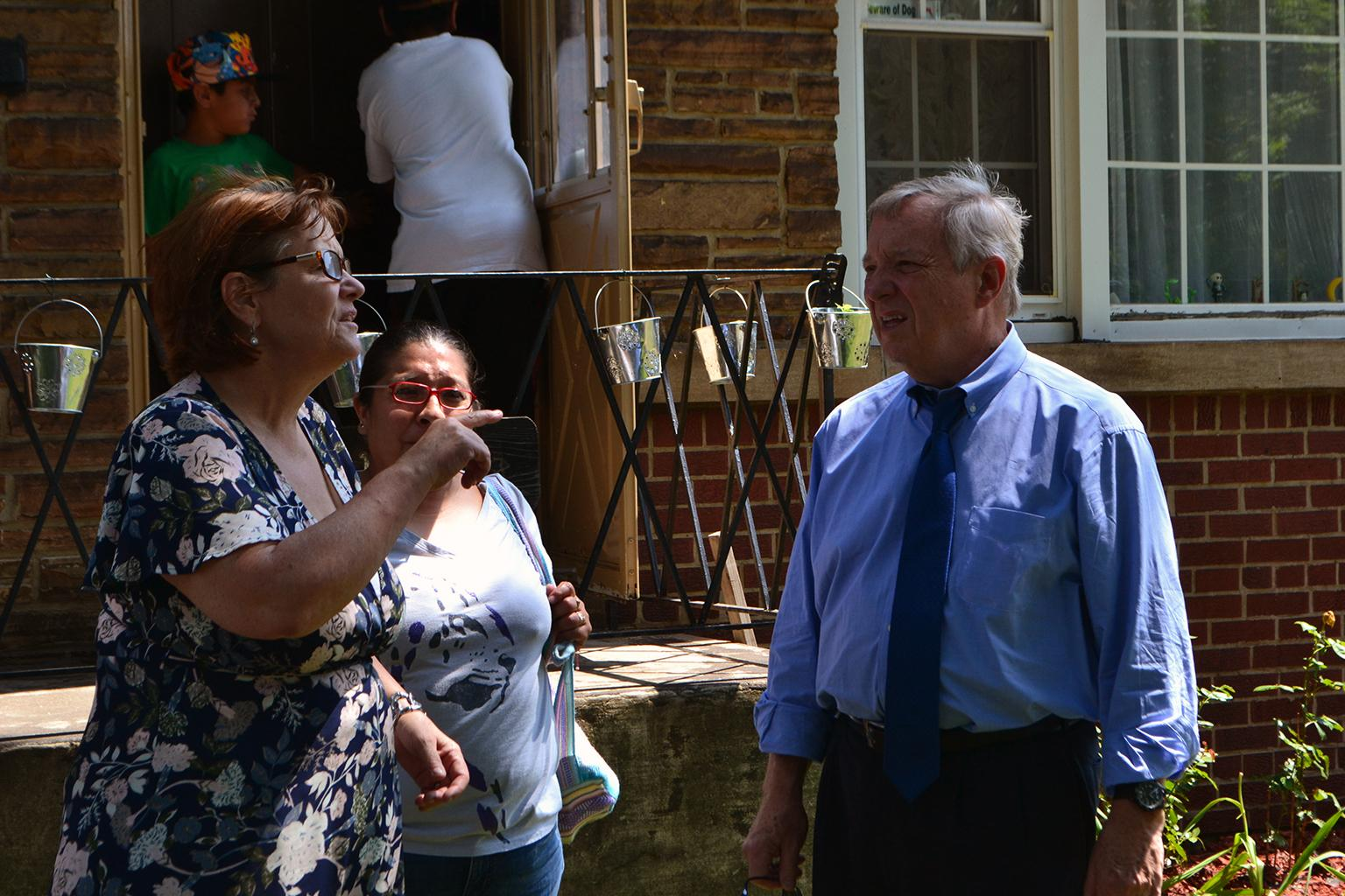 U.S. Sen. Dick Durbin talks with a Southeast Side resident outside of her home Thursday. (Alex Ruppenthal / Chicago Tonight)