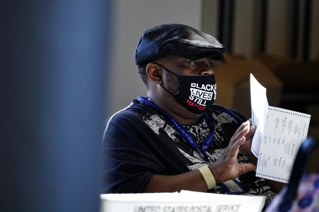 In this Nov. 4, 2020, file photo, an election worker holds a ballot as vote counting in the general election continues at State Farm Arena in Atlanta.  (AP Photo / Brynn Anderson, File)