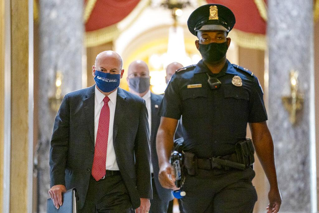 In this Aug. 5, 2020, file photo Postmaster General Louis DeJoy, left, is escorted to House Speaker Nancy Pelosi's office on Capitol Hill in Washington. (AP Photo / Carolyn Kaster, File)