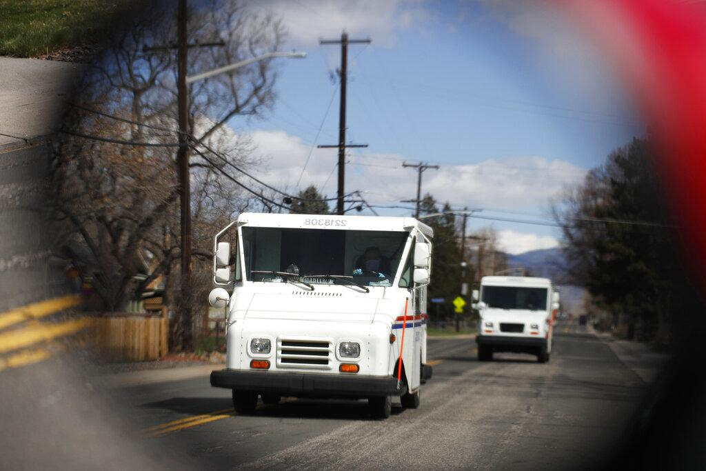 In this March 31, 2020, file photo United States Post Office delivery trucks are reflected in the side mirror of a vehicle as postal delivers set off on their daily rounds in Arvada, Colo. (AP Photo / David Zalubowski, File)