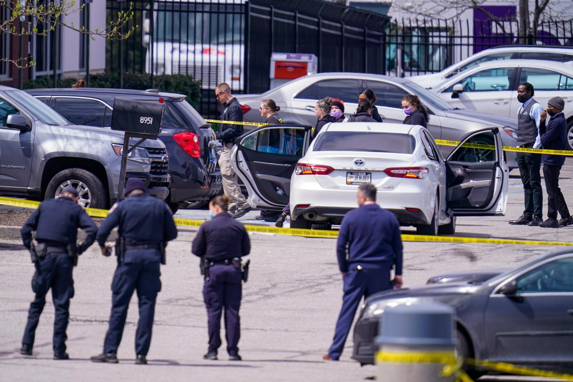 Law enforcement confer at the scene, Friday, April 16, 2021, in Indianapolis, where multiple people were shot at a FedEx Ground facility near the Indianapolis airport. (AP Photo / Michael Conroy)