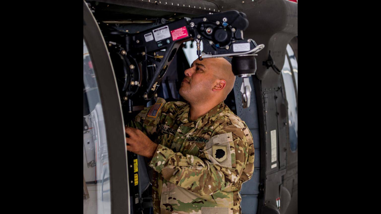 Sgt. Andres Salazar inspects an internal hoist on the UH-60 Blackhawk helicopter at the Kankakee Army Aviation Support Facility on Sept. 12, 2018. (Sgt. Stephen Gifford / Illinois National Guard)