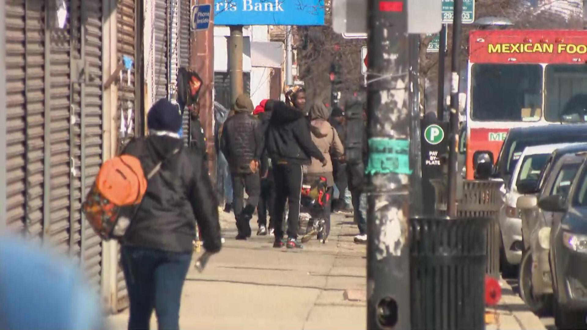 People walk along a busy street in Garfield Park on Wednesday, April 1, 2020. (WTTW News)
