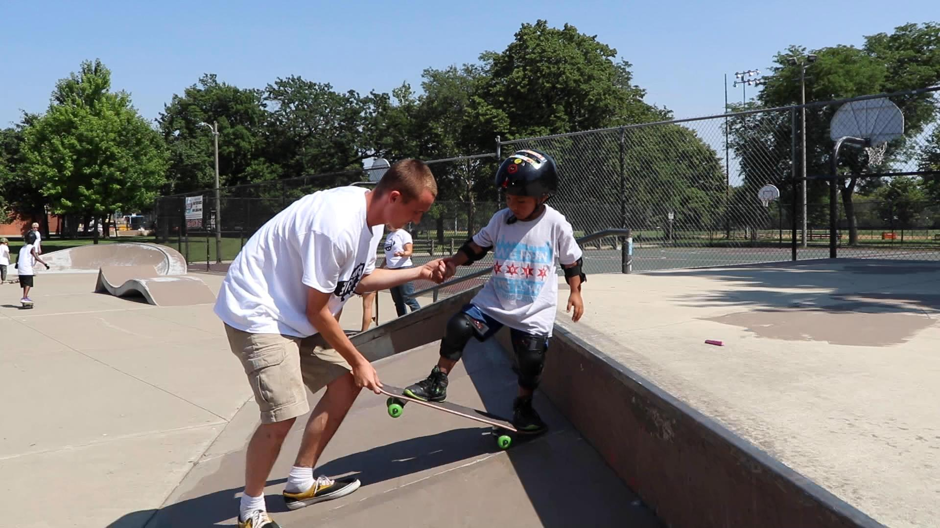 "Skate instructor Grant Katula helps a young skater ""drop in"" on a ramp at Piotrowksi Skate Park. (Evan Garcia / WTTW News)"