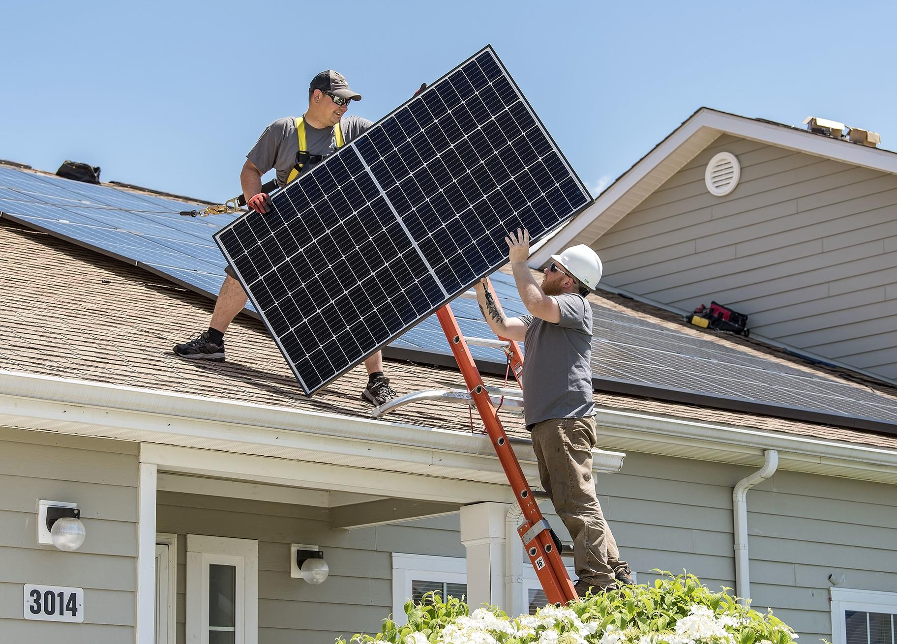 Wyatt Whelan, left, and Eric Roberts move a photovoltaic panel to a roof on May 11, 2018, in the Dover Family Housing community at Dover Air Force Base in Delaware. (Roland Balik / U.S. Air Force)