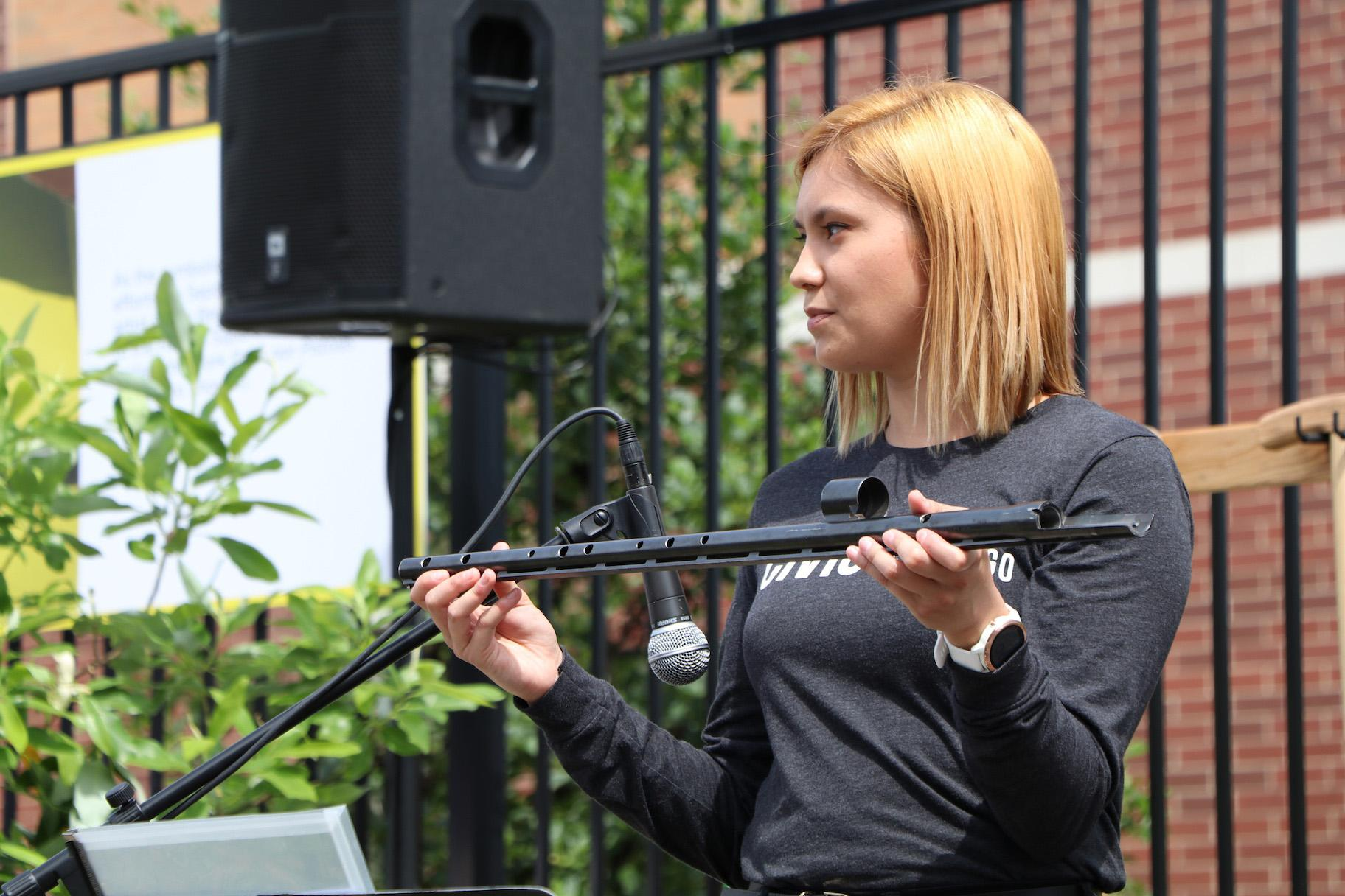 Alexandria Hoffman holds a flute made from a rifle's barrel. (Evan Garcia / WTTW)