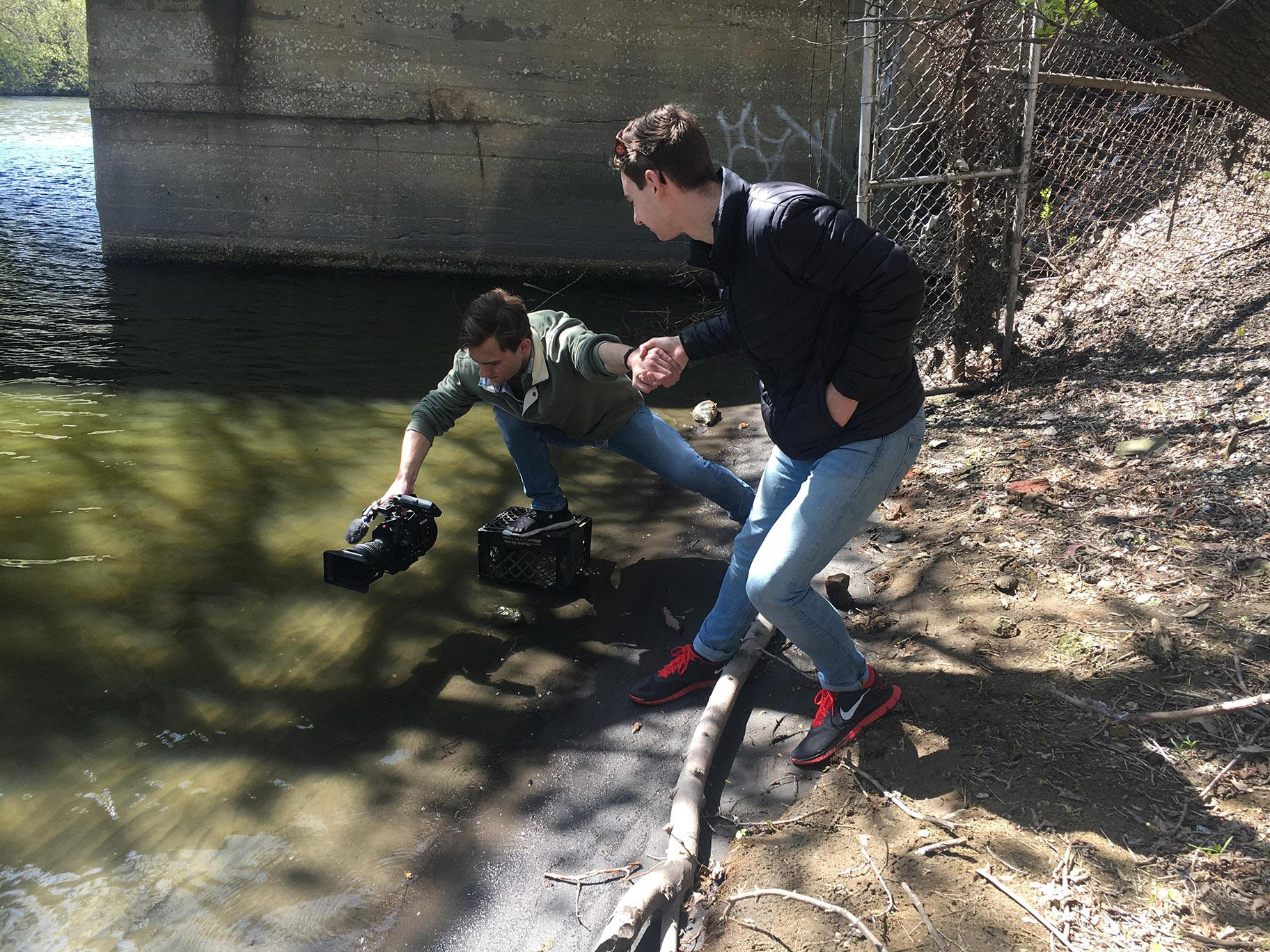 DePaul University student journalists shooting video of the bubbles in the creek.