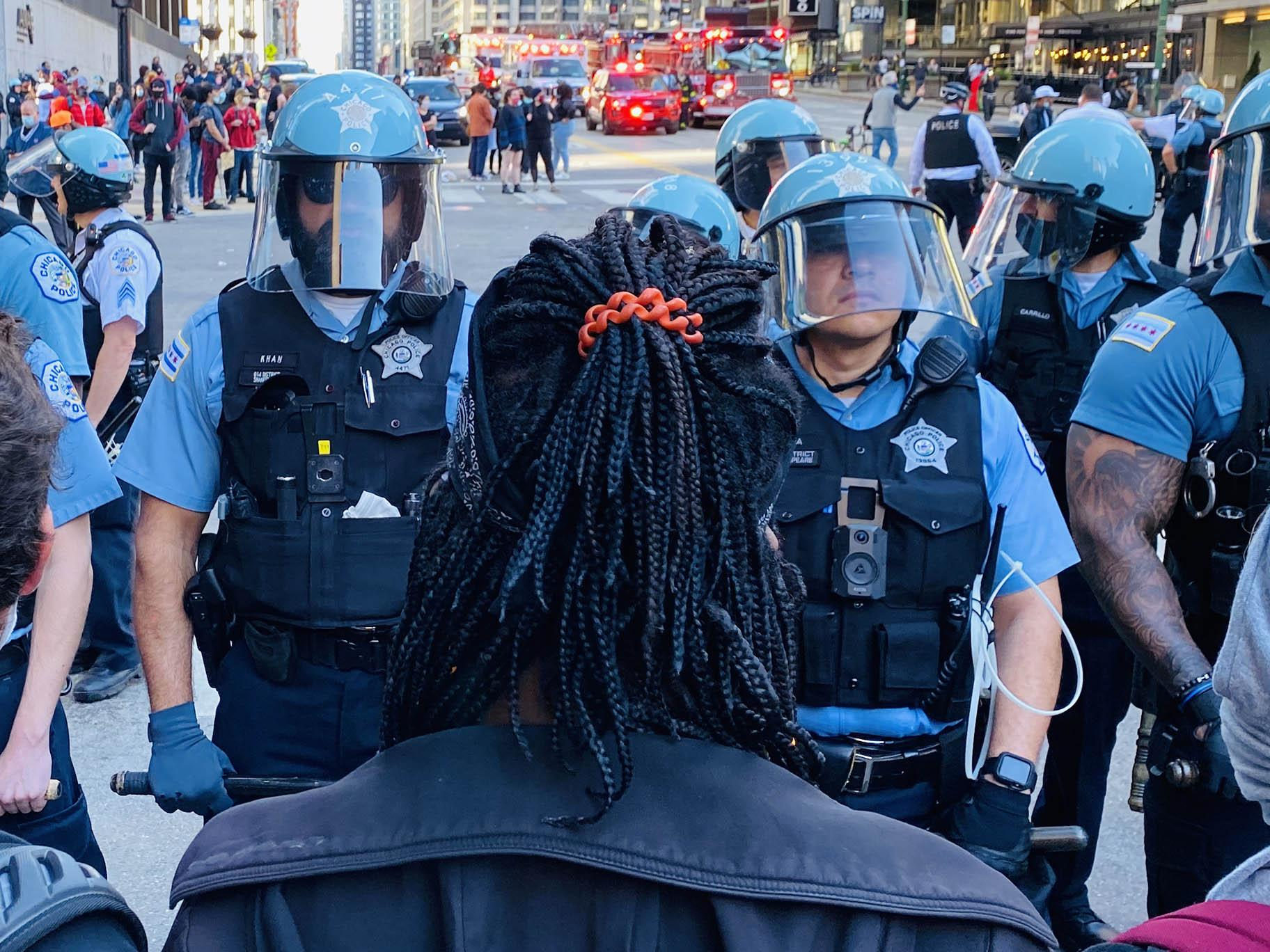 A protester faces a line of police officers in Chicago on Saturday, May 30, 2020. (Hugo Balta / WTTW News)