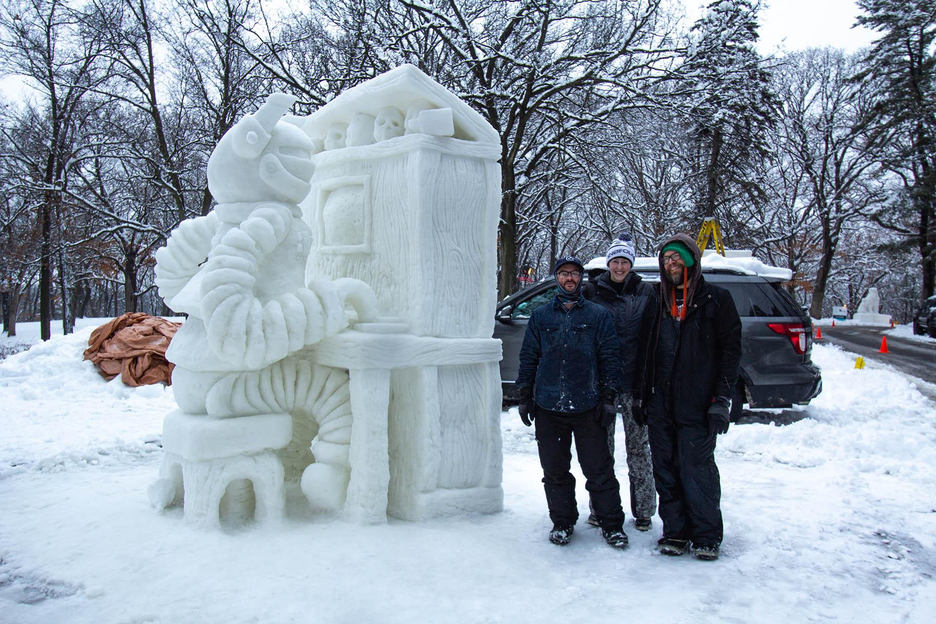 "The winners of the 34th annual Illinois Snow Sculpting Competition, a team called Cave People from Space, pose next to their sculpture ""Player Piano"" on Saturday. (Courtesy Rockford Park District)"