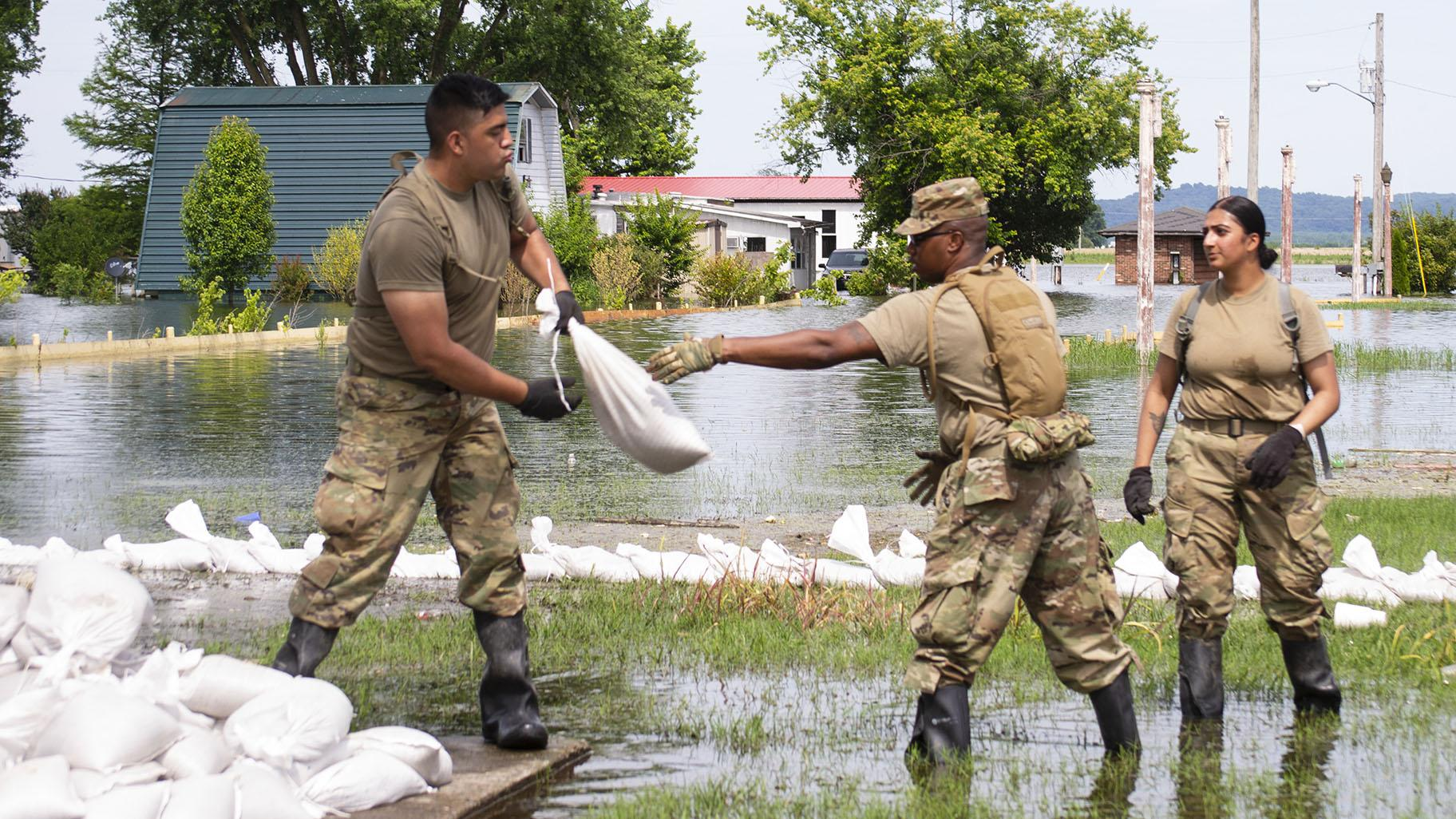 Illinois National Guard soldiers move sandbags through flood waters at East Cape Girardeau, Illinois, on June 12, 2019, as they construct a sandbag levee to control flooding in the community. (Barbara Wilson / Illinois National Guard)