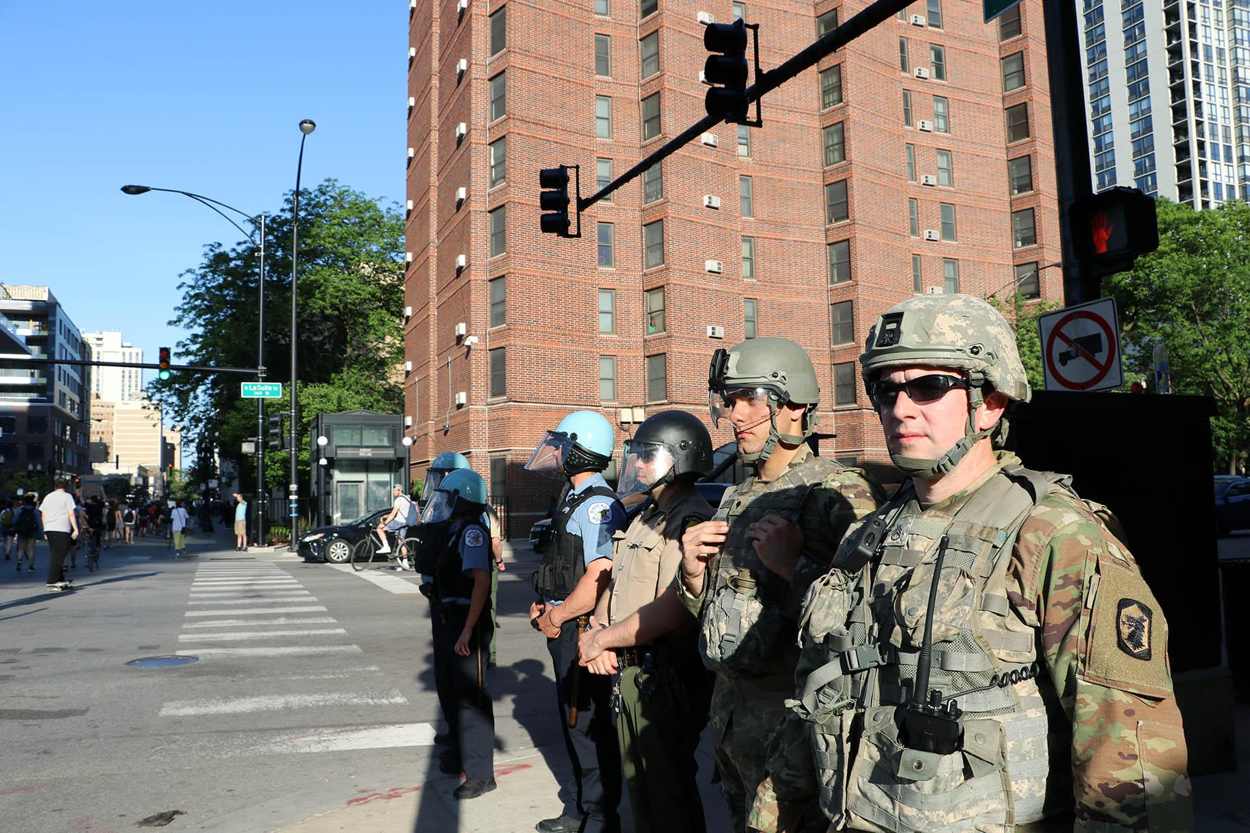 Illinois National Guard officers watch a protest in Old Town on June 6, 2020, one of many in the city and across the U.S. sparked by the death of George Floyd while in Minneapolis police custody. (Evan Garcia / WTTW News)