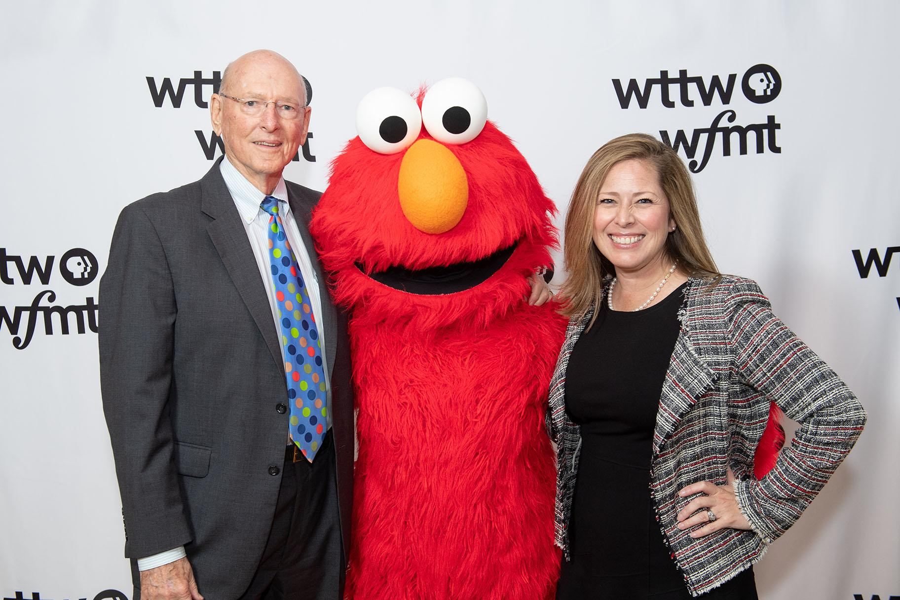 """Jim Mabie and Sandra Cordova Micek, president and CEO of WTTW and WFMT, pose with Elmo from """"Sesame Street."""" (WTTW)"""