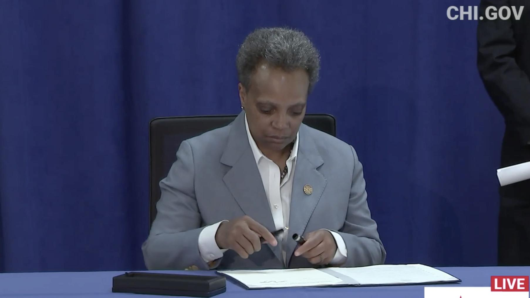 Mayor Lori Lightfoot signs an executive order ensuring all Chicago residents have equal access to COVID-19 aid programs regardless of citizenship status on Tuesday, April 7, 2020. (Chicago Mayor's Office / Facebook photo)