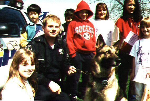 Former Oak Brook Police Officer Randy Mucha poses with K-9 Officer Marlo and a group of children. (Randy Mucha)