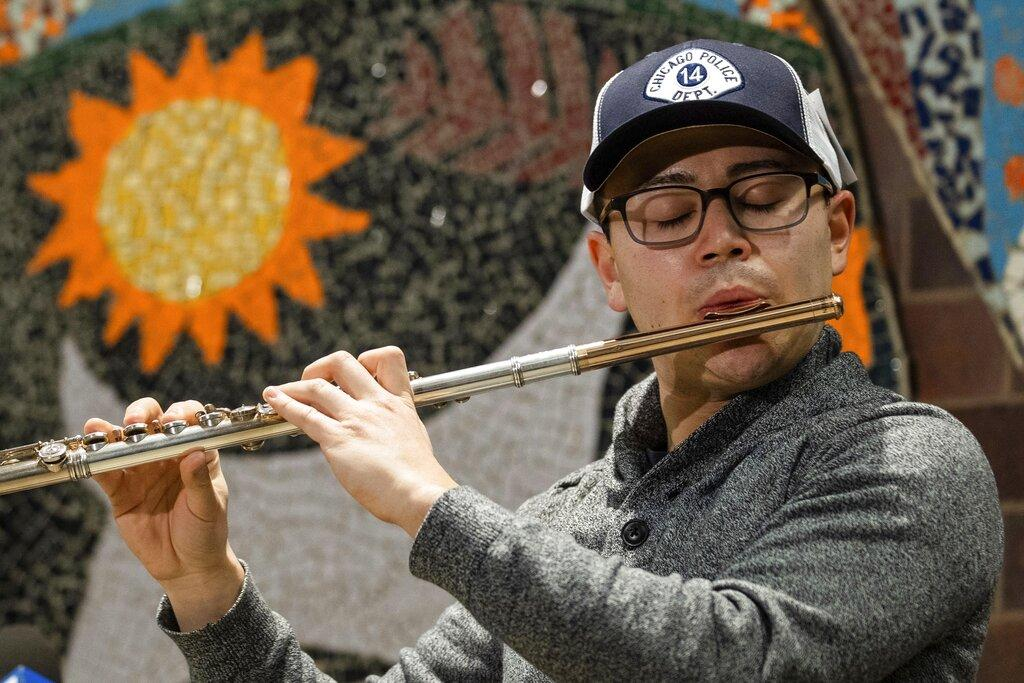 Donald Rabin plays the flute after Detective George Hilbring retrieved and returned it to him during a news conference at the 14th District Police Station on Thursday, Feb. 4, 2021. (Pat Nabong / Chicago Sun-Times via AP)