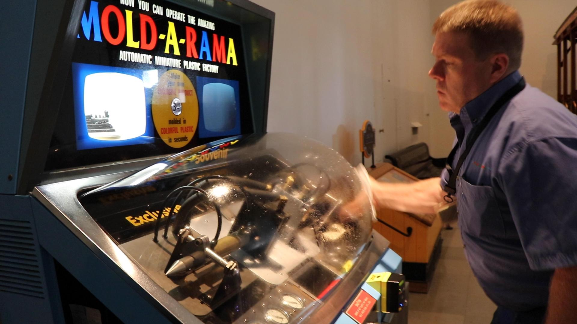 Paul Jones of Mold-A-Rama Inc. checks on a souvenir machine at the Museum of Science and Industry. (Evan Garcia / WTTW News)