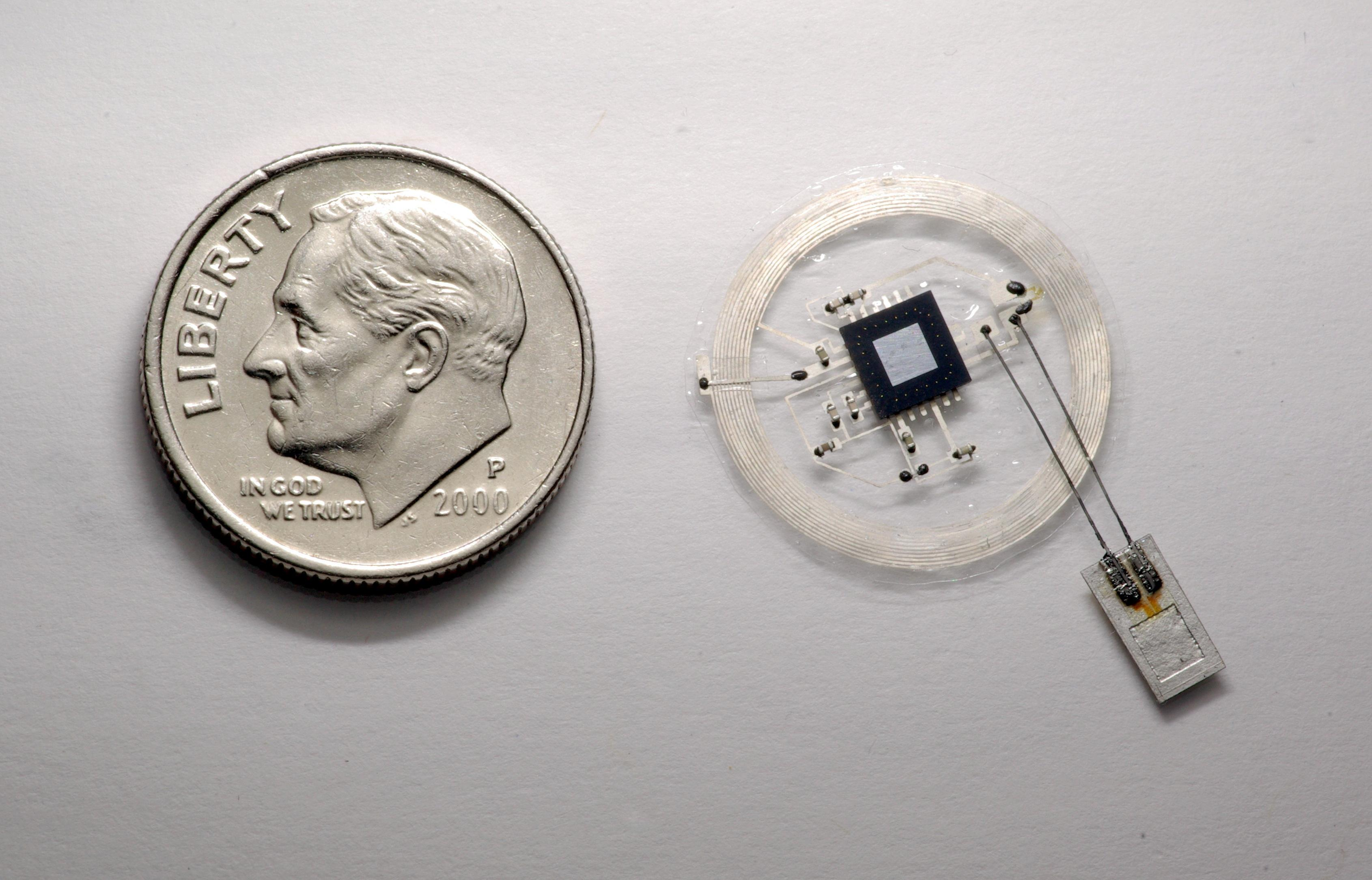 The small sensor (pictured on the right) connects to an embeddable wireless transmitter that lies on top of the skull.  (John A. Rogers)
