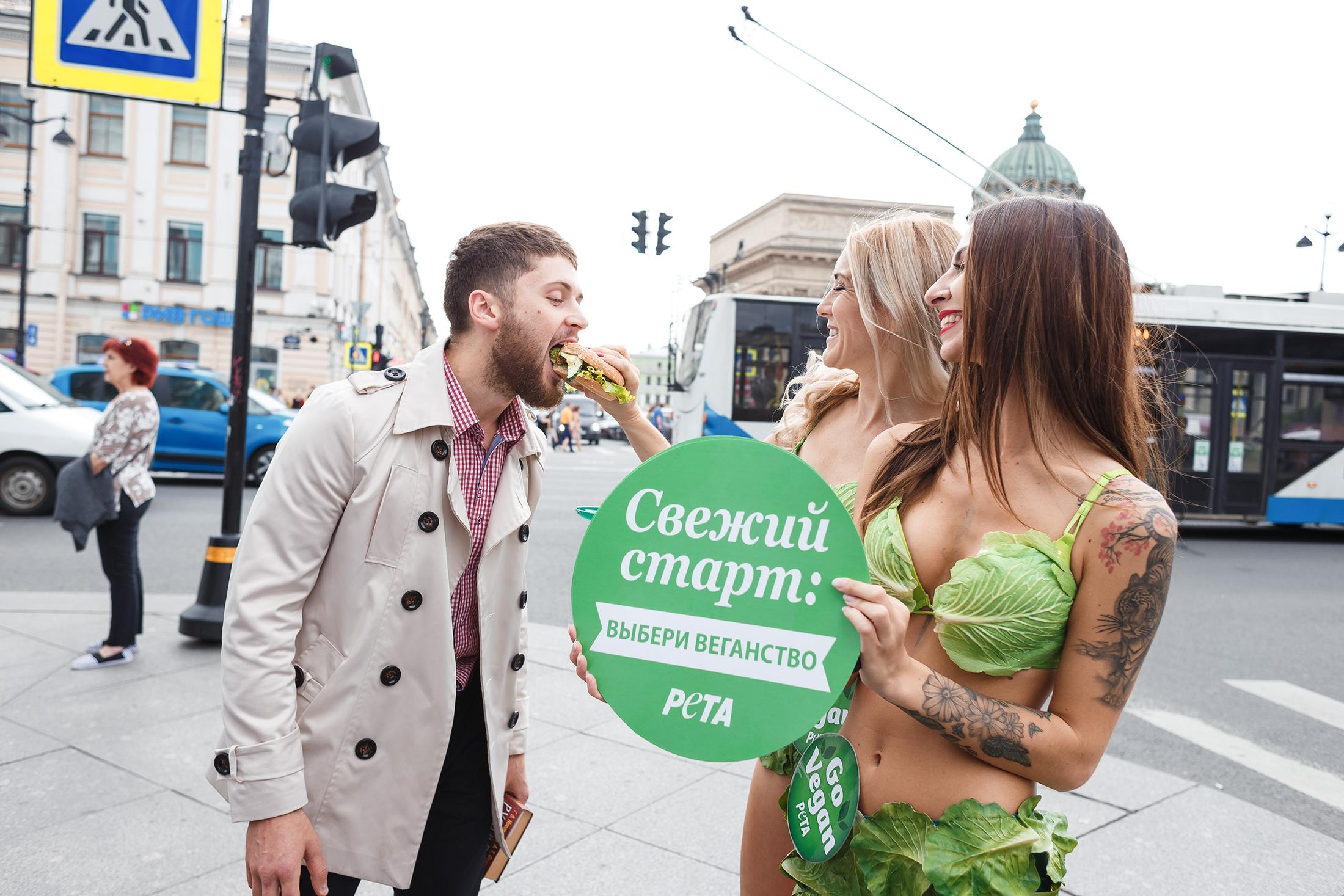 "South Elgin native Mysti Lee, right, watches as another member of PETA's ""Lettuce Ladies"" feeds a vegan sandwich to a passerby in St. Petersburg, Russia. (Dmitry Korotkov / PETA)"